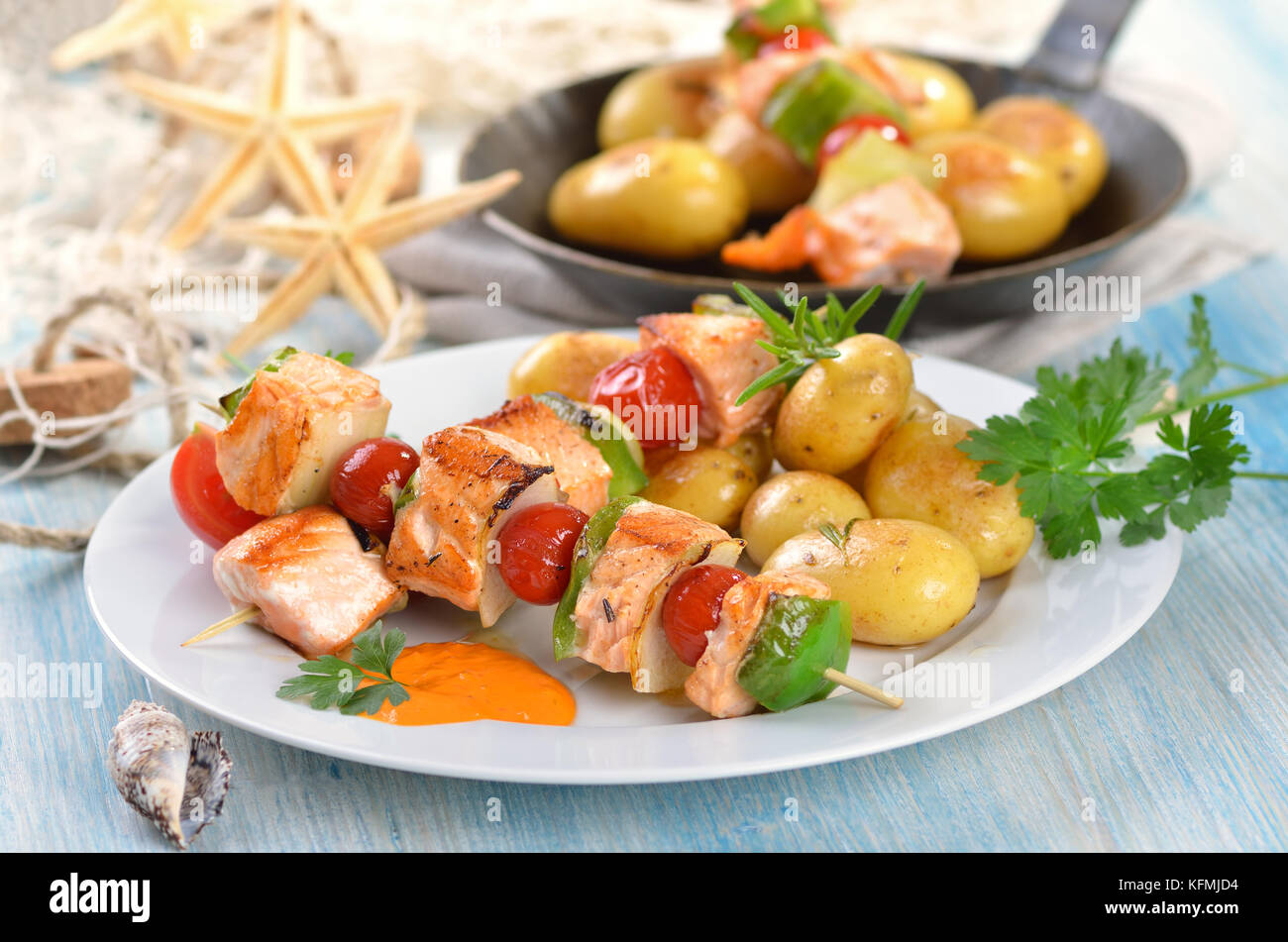Fried salmon skewers with vegetables and small fried potatoes with rosemary, a pan in the background - Stock Image