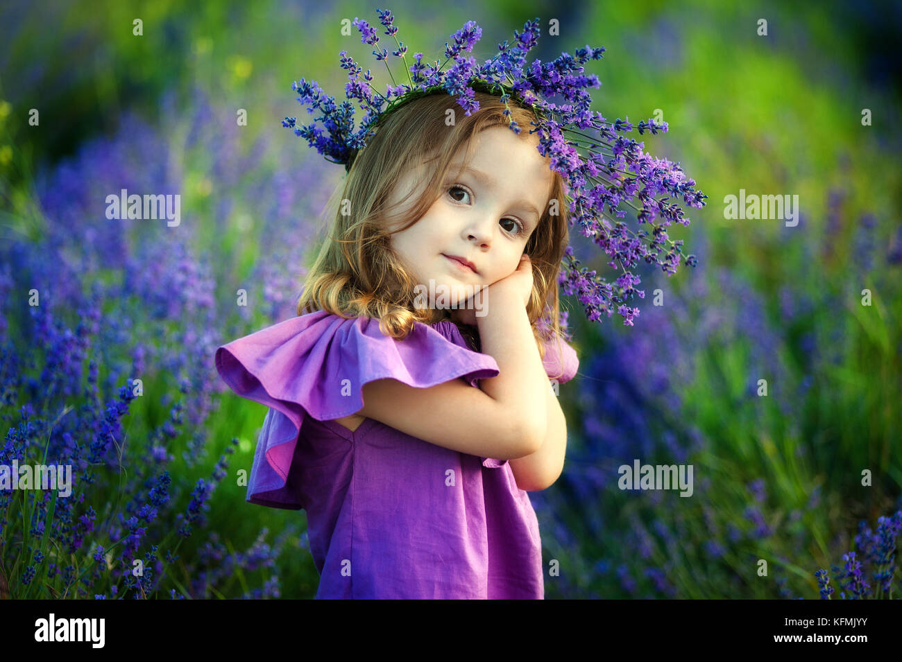 Cute smiling little girl with flower wreath on the meadow at