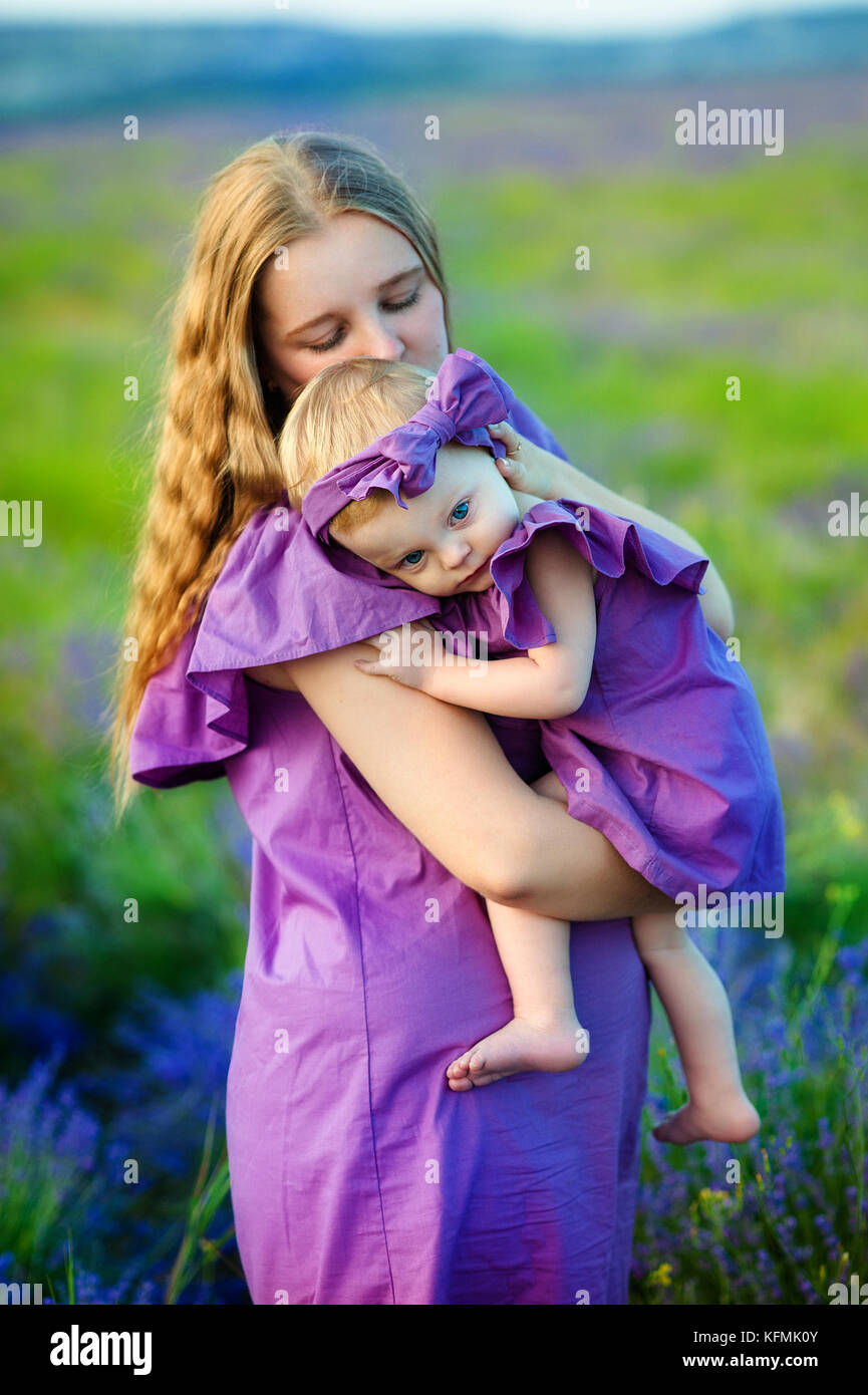Mother hugs her little daughter in the rays of the setting sun, wearing long lilac dresses - Stock Image