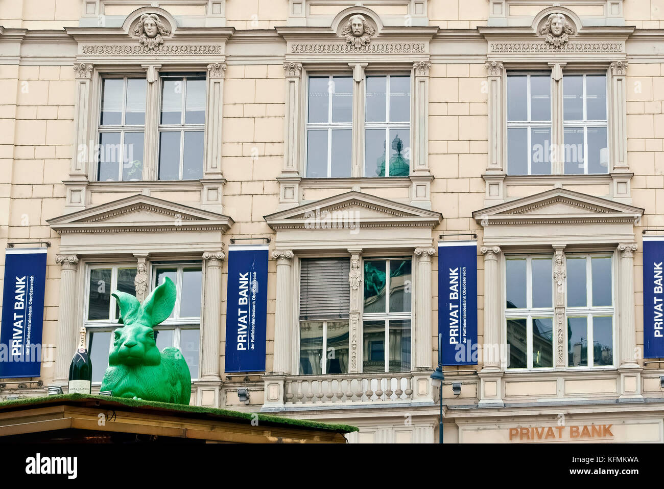 Privat bank at Operngasse. On rooftop: big green plastic rabbit sculpture, Cracking art project Installation. Big - Stock Image
