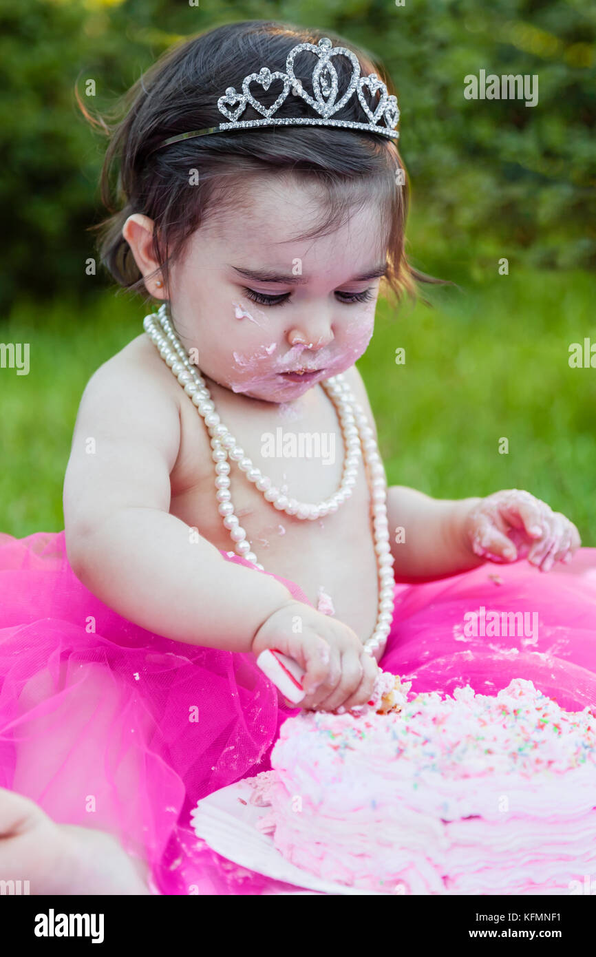 Happy baby toddler girl in first birthday anniversary party, with dirty face making a mess of pink cake with candle. - Stock Image