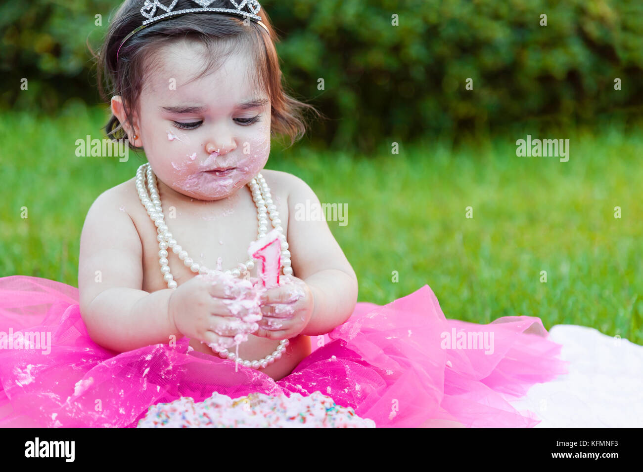 Baby toddler girl first birthday anniversary party, playing with candle, dirty face and making a mess of pink cake - Stock Image