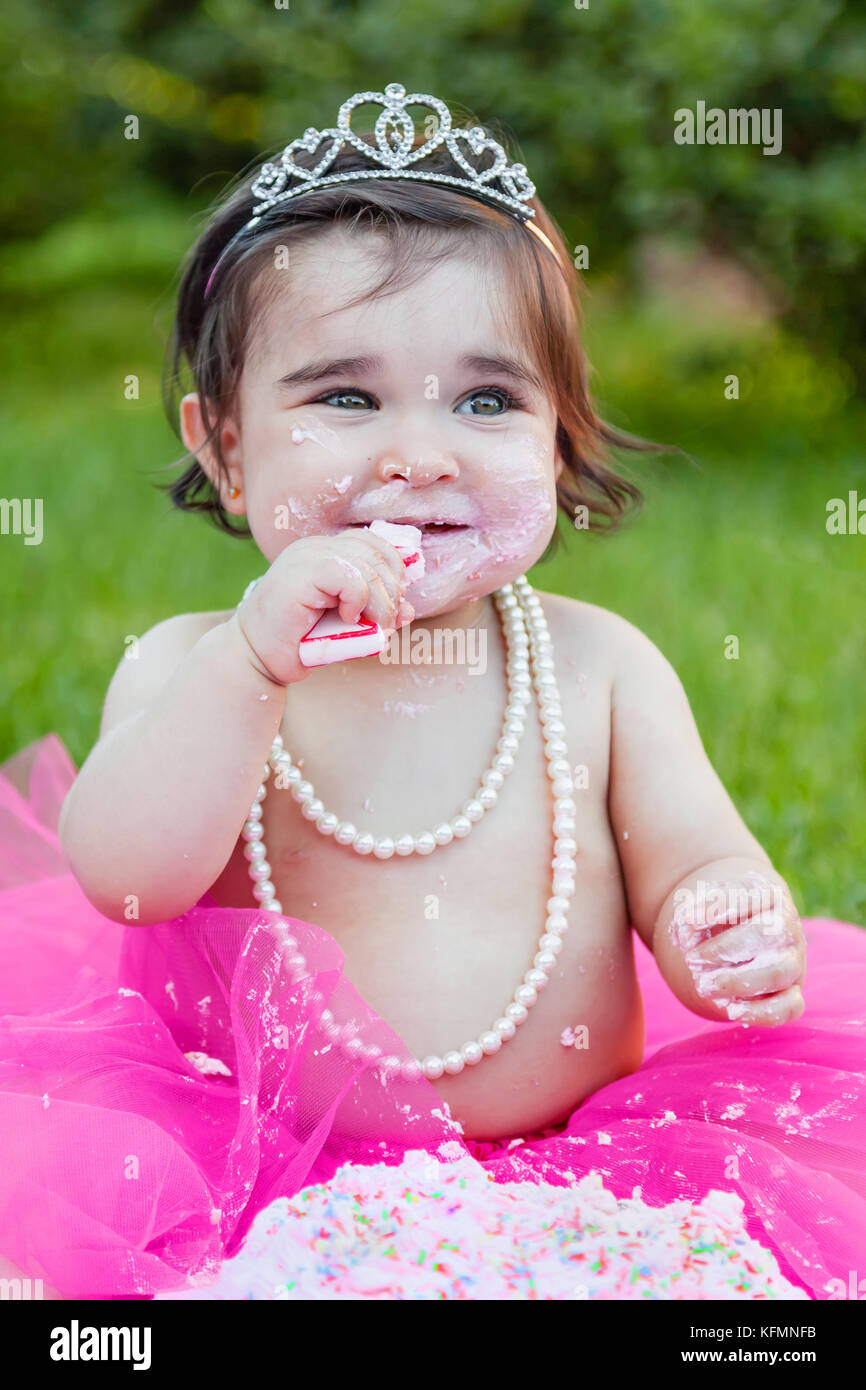 Smiling happy baby toddler girl celebrating first birthday anniversary party. Holding and chewing candle with dirty - Stock Image