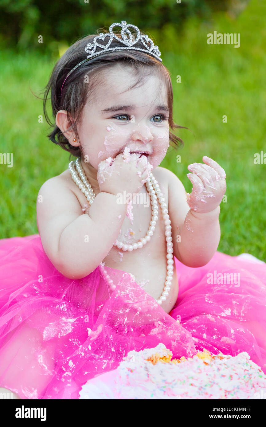 Smiling happy baby toddler girl first birthday anniversary party. Licking hand with face dirty from pink cake. Princess - Stock Image