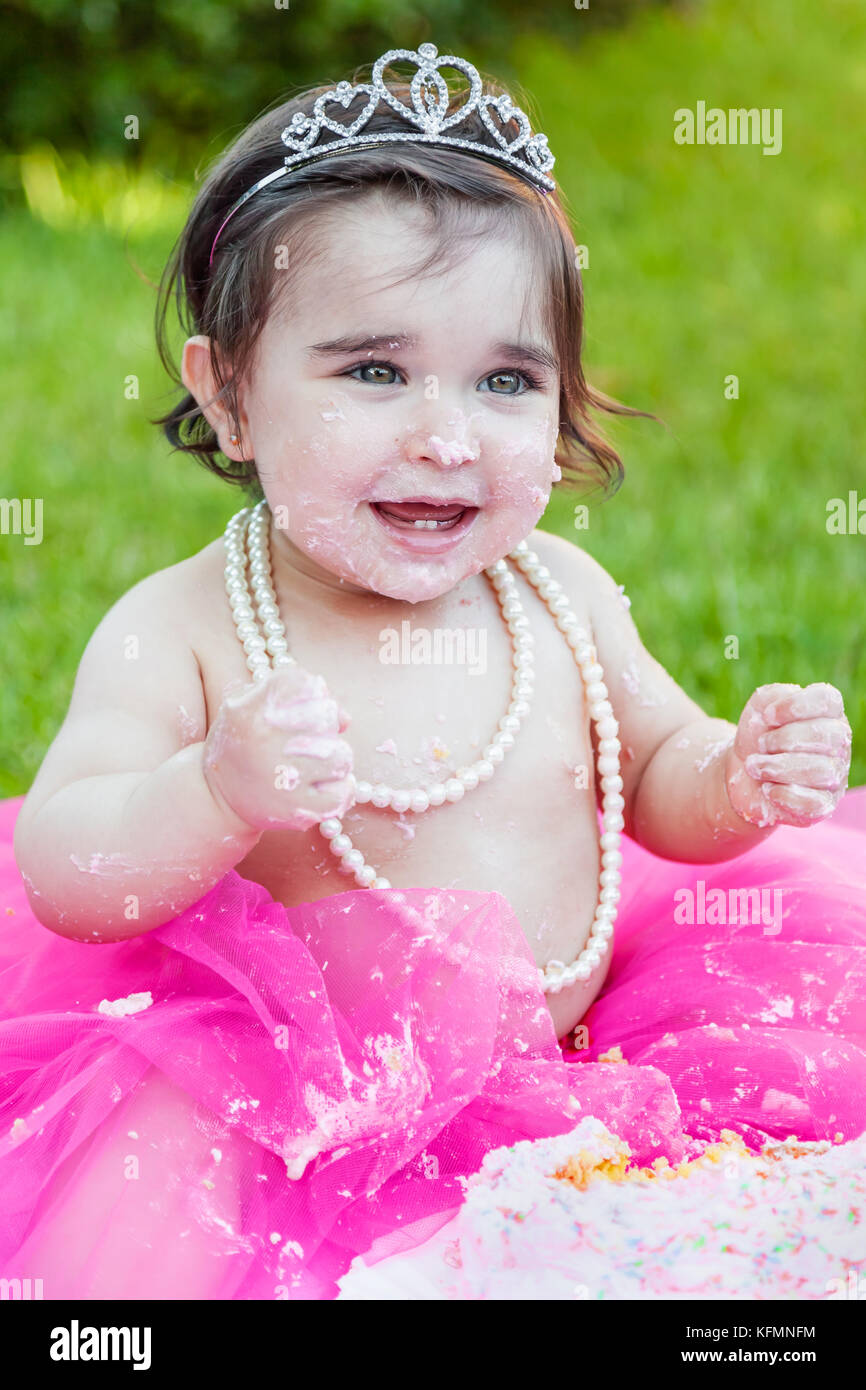 Smiling happy baby toddler girl first birthday anniversary party. Laughing with face and hands dirty from smashed - Stock Image