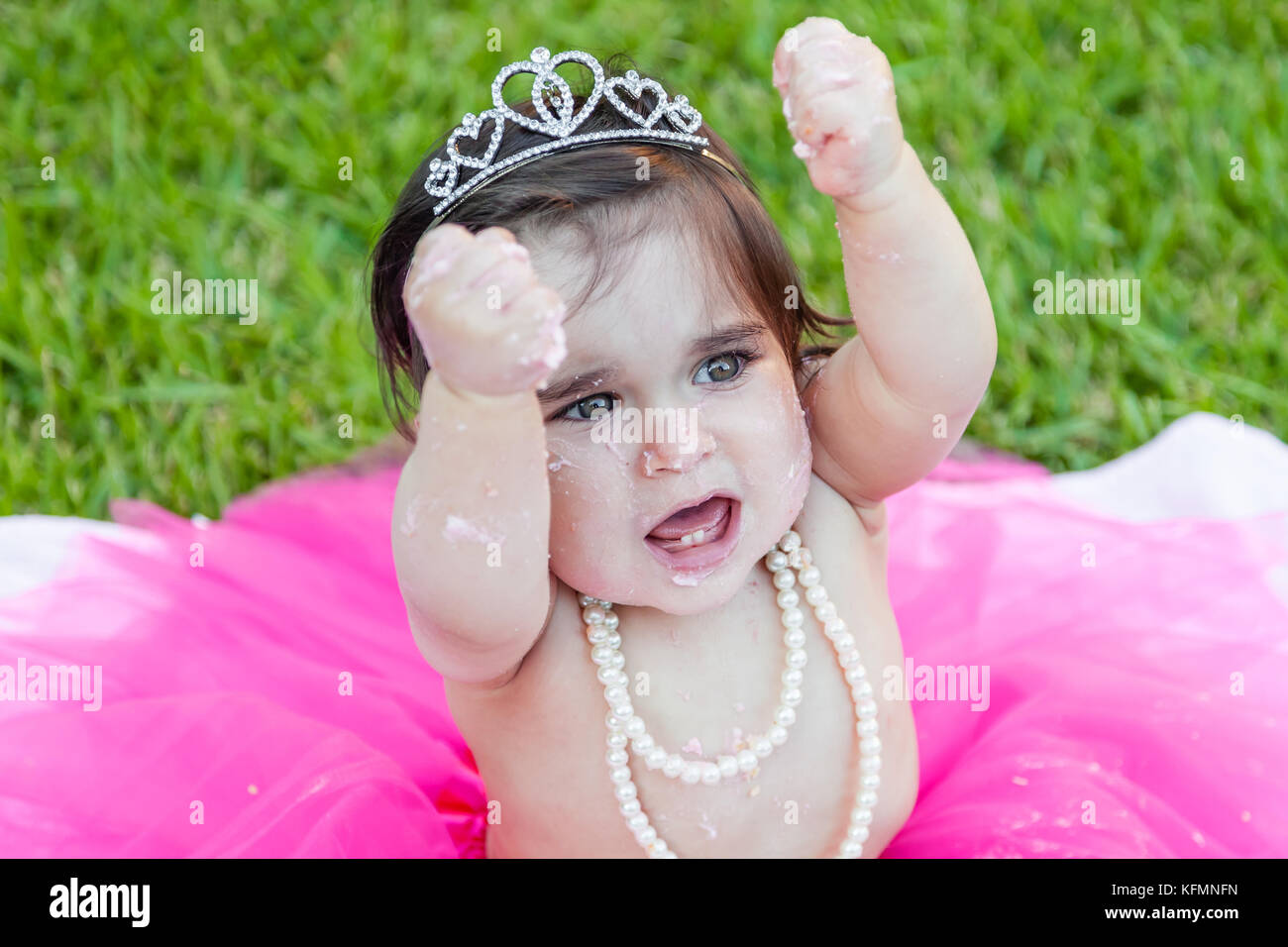 Happy excited baby toddler girl first birthday anniversary party. Shouting hooray with raised fists in joy. Face - Stock Image