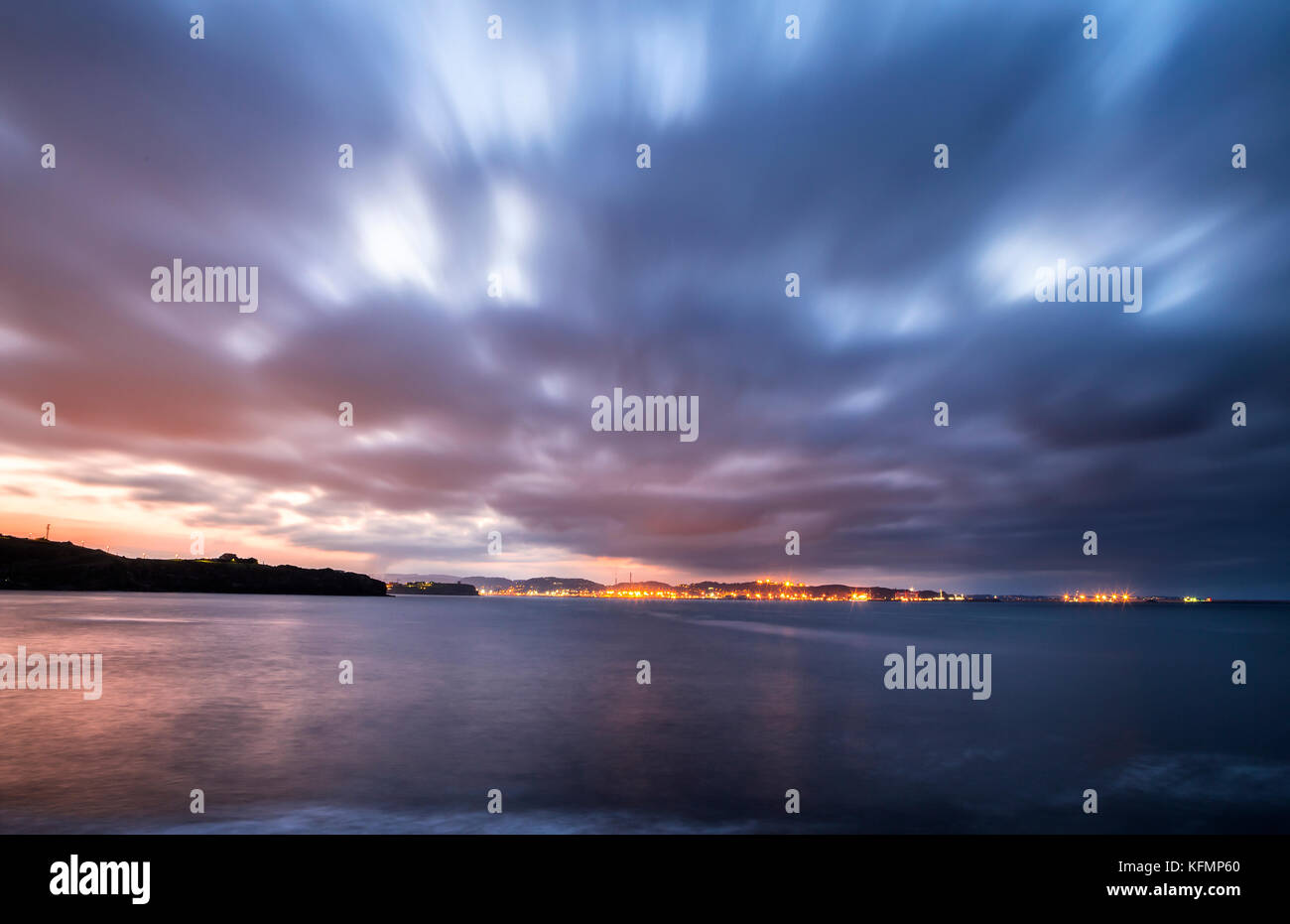 Sunset over city lights with moving clouds - Gijón, Asturias Spain - Stock Image