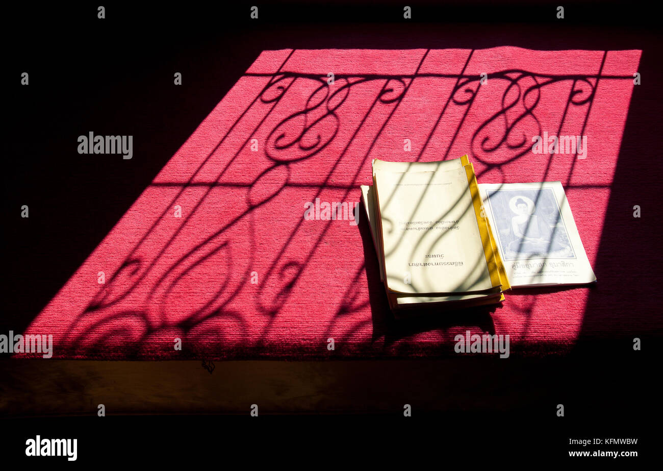 Buddhist text books lay in window silhouette - Stock Image