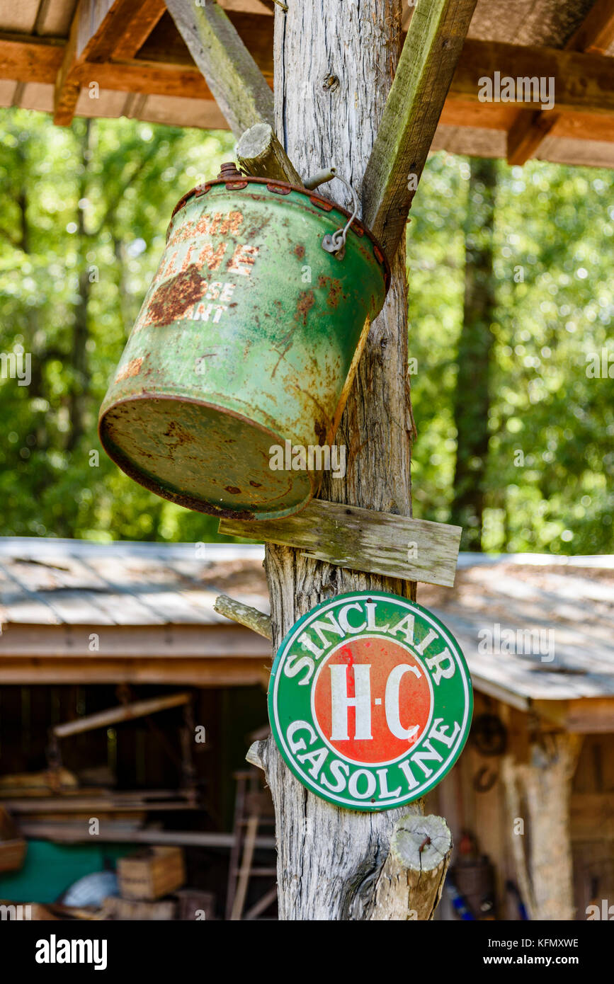 An old green antique gasoline can hangs next to a sign for Sinclair HC gasoline in rural Alabama, USA. - Stock Image