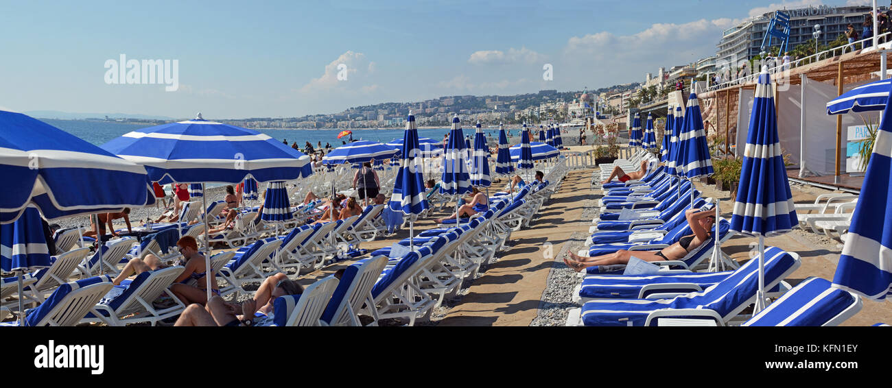 Nice, France - September 27, 2017: Blue Umbrellas and deck chairs on the Beach at Nice France - Stock Image