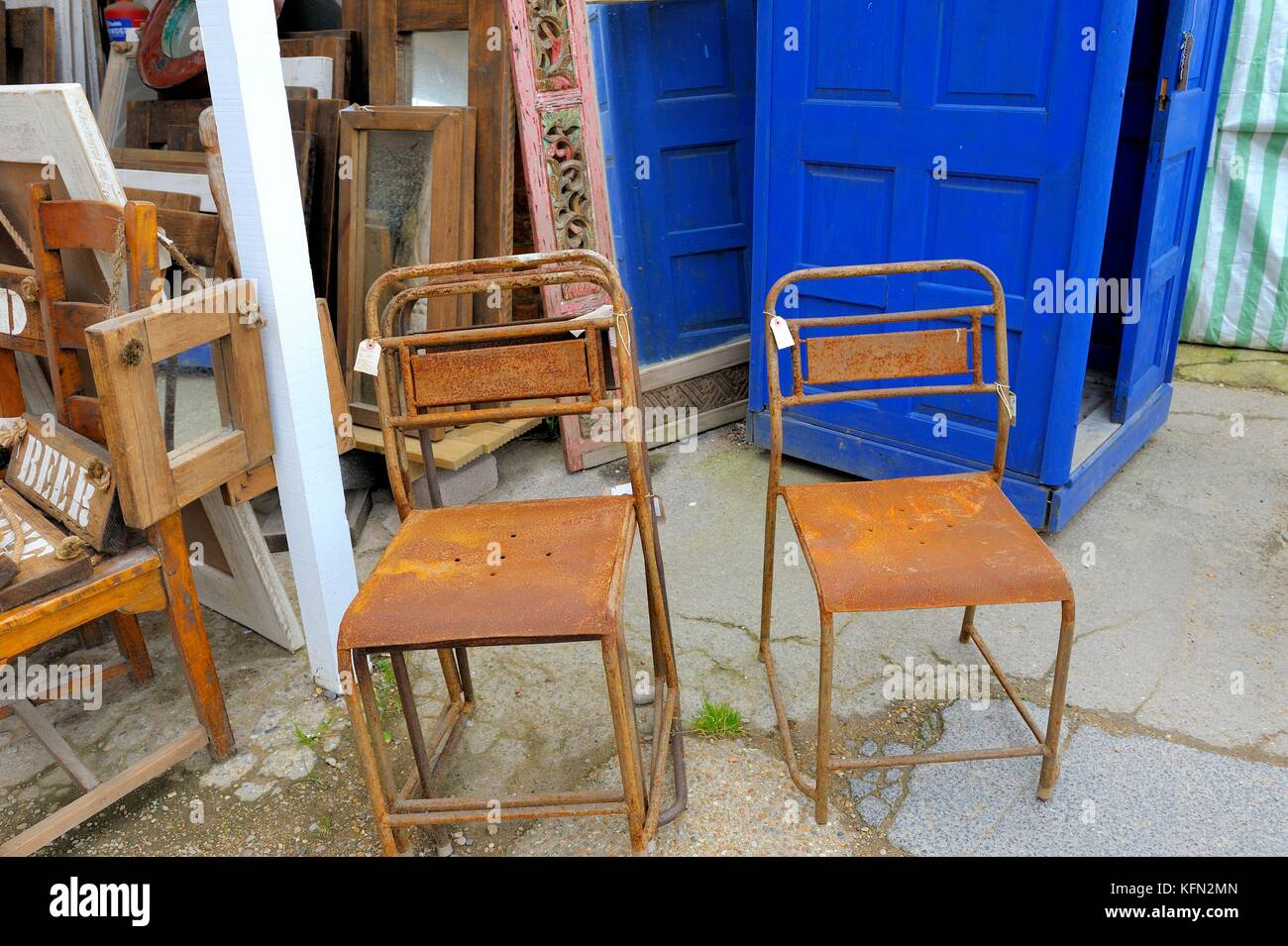 Rusty chairs for sale on a 2nd hand market stall - Stock Image