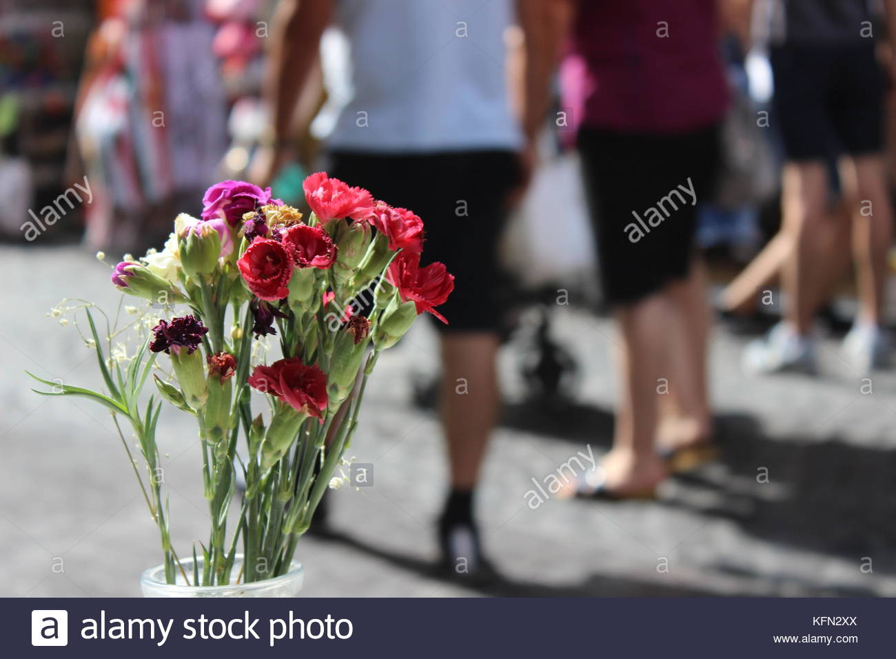 Depth of field multi colored flowers in busy street of people - Stock Image