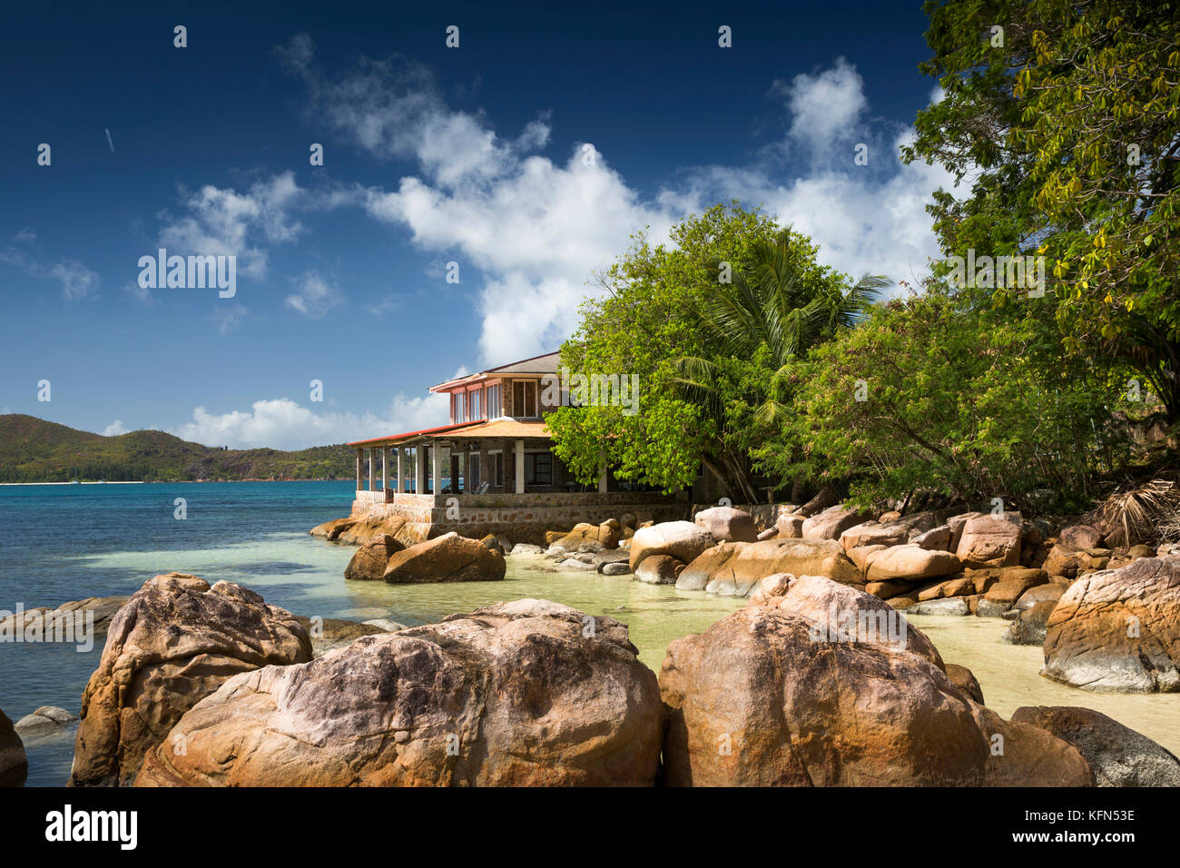 The Seychelles, Praslin, Anse Posession, Coin d'Or Guest House on headland beyond rocks - Stock Image