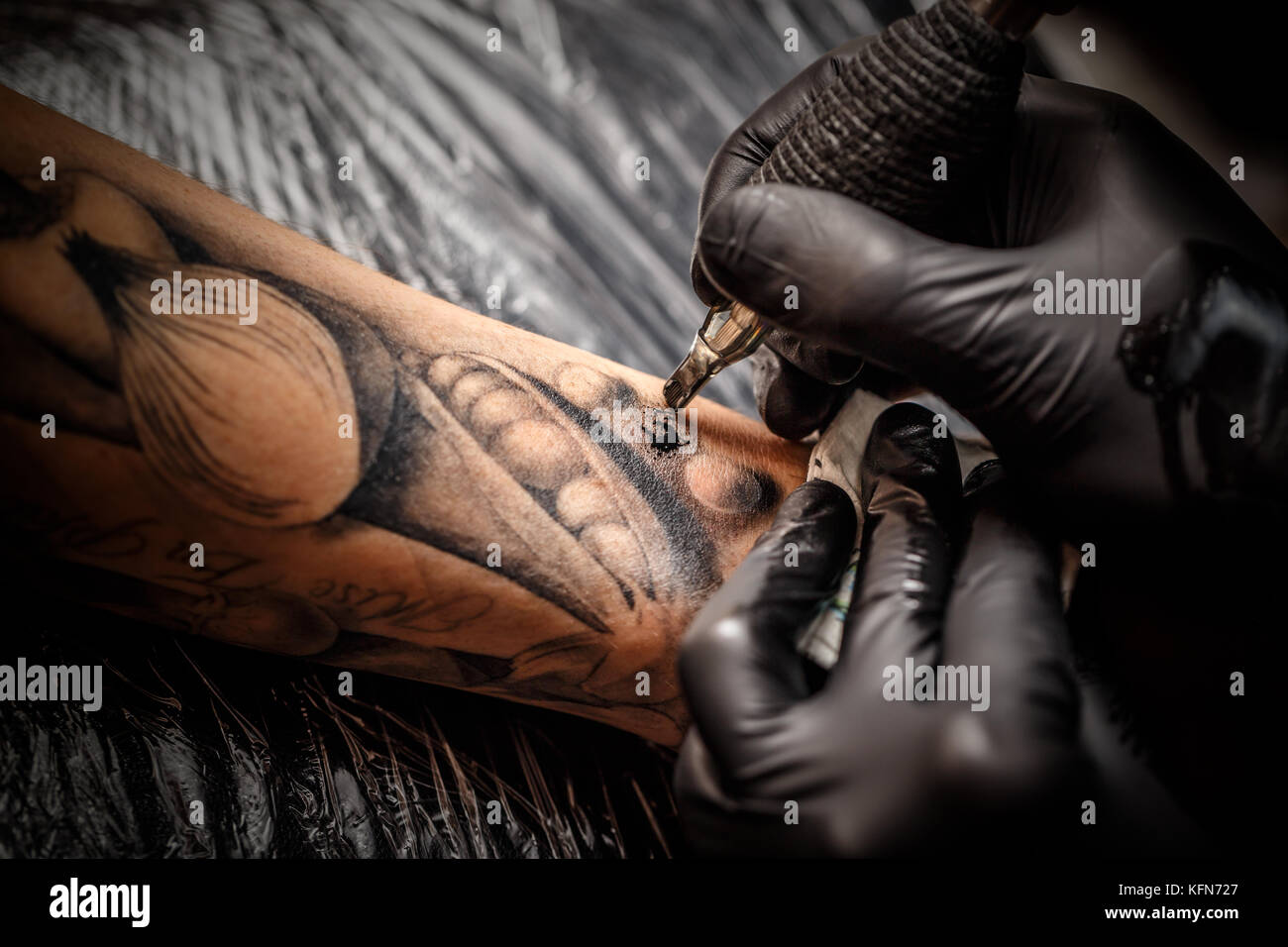 A professional tattoo artist introduces black ink into the skin using a needle from a tattoo machine. - Stock Image
