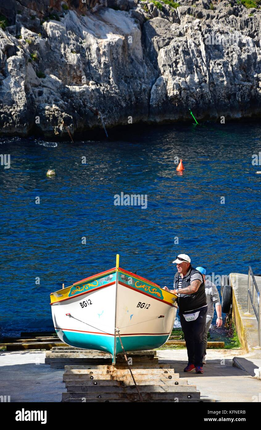 Men pulling a traditional Dghajsa water taxi up a ramp for mooring at the departure point, Blue Grotto, Malta, Europe. - Stock Image