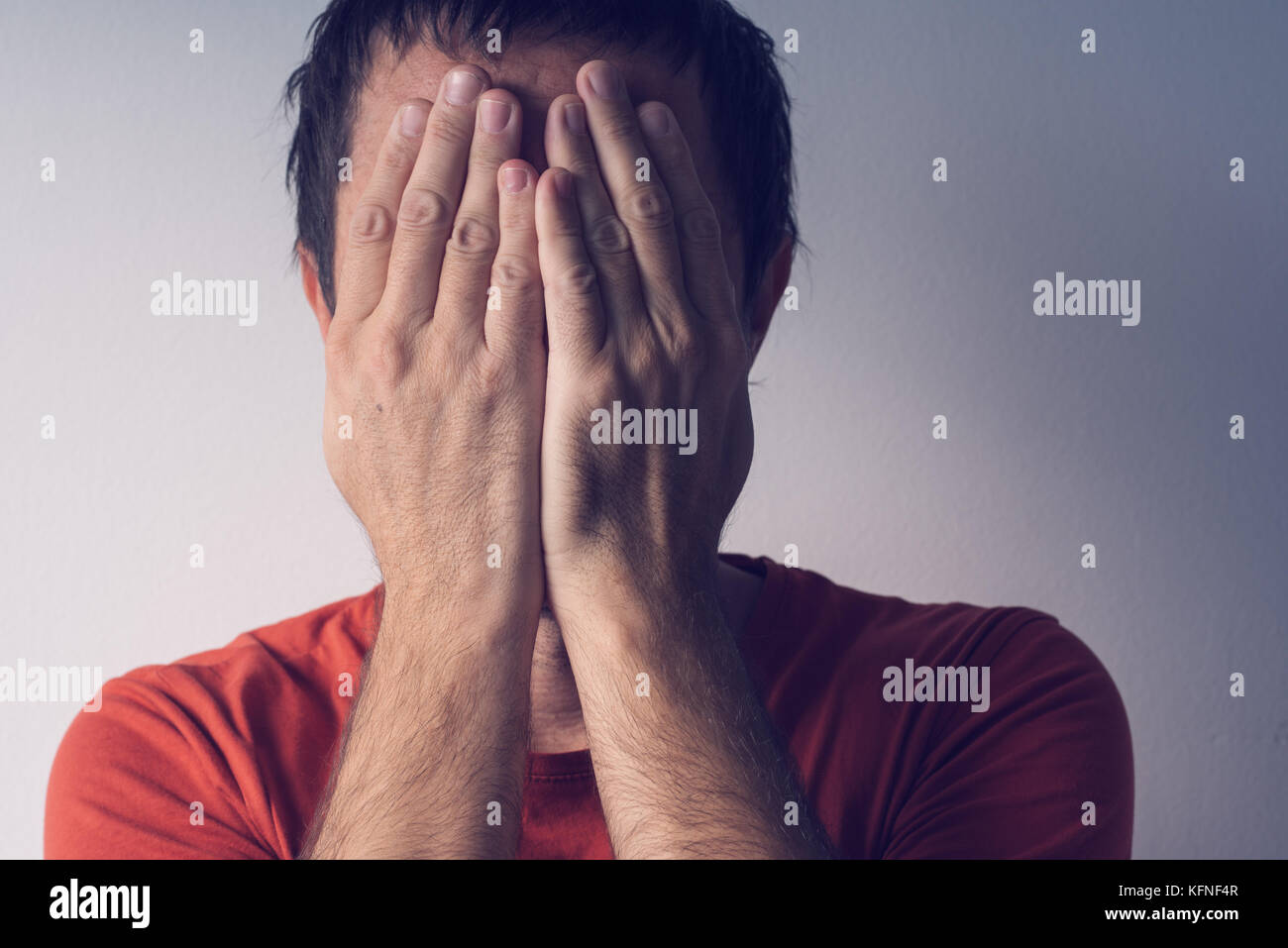 Ashamed man covering face. Shame, disgrace and embarrassment - Stock Image