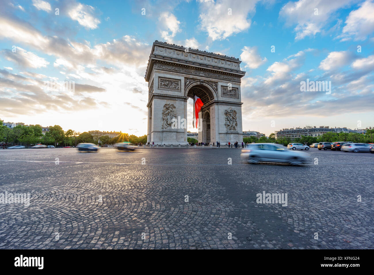 Wide Arc de Triomphe and blurred traffic at sunset - Stock Image