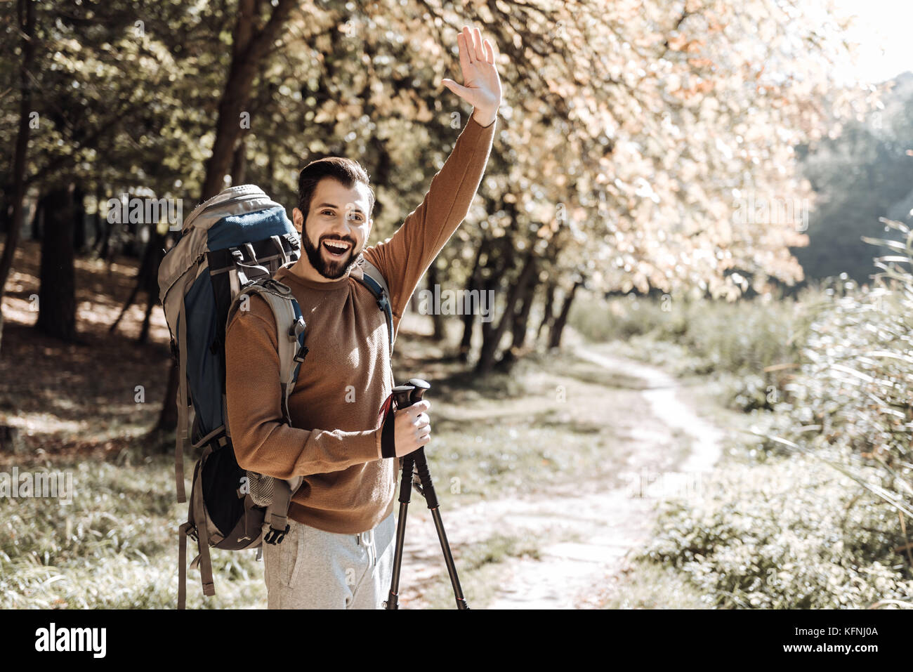 Cheerful traveller waving his hand - Stock Image