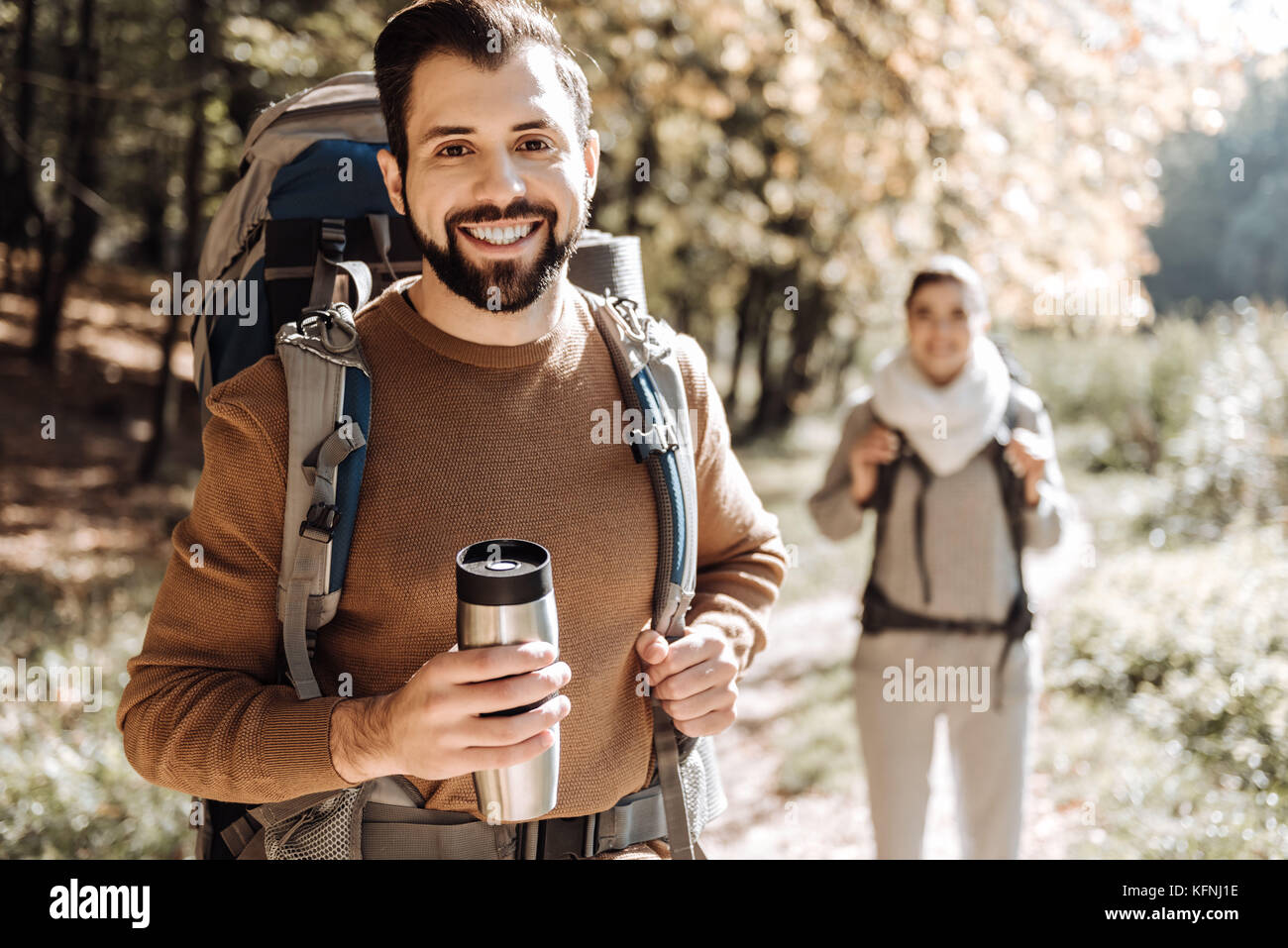 Close up of positive traveller with a thermos bottle - Stock Image