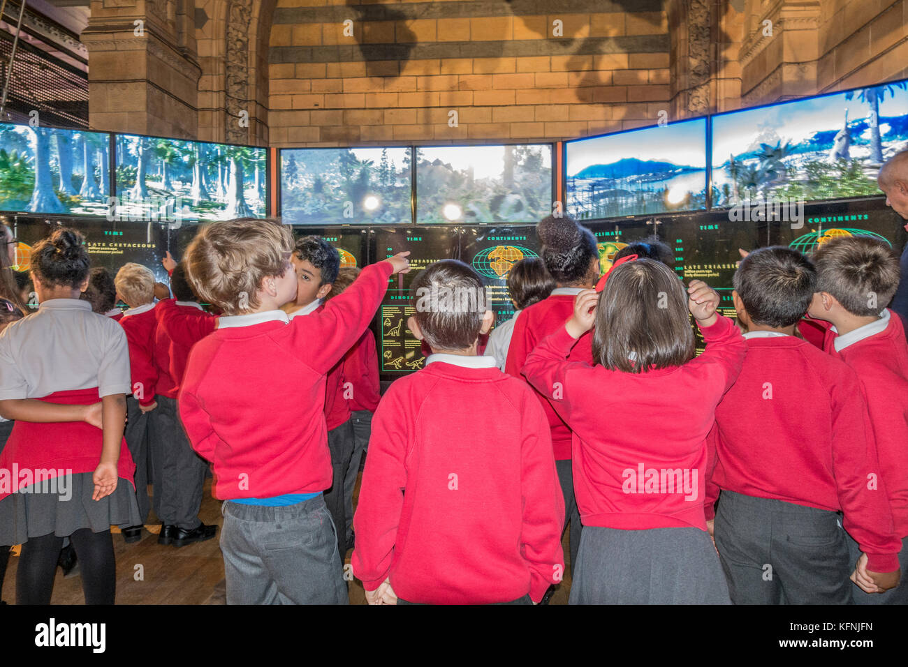 Excited schoolchildren in uniform, on a school trip, viewing information displays at the Natural History Museum - Stock Image