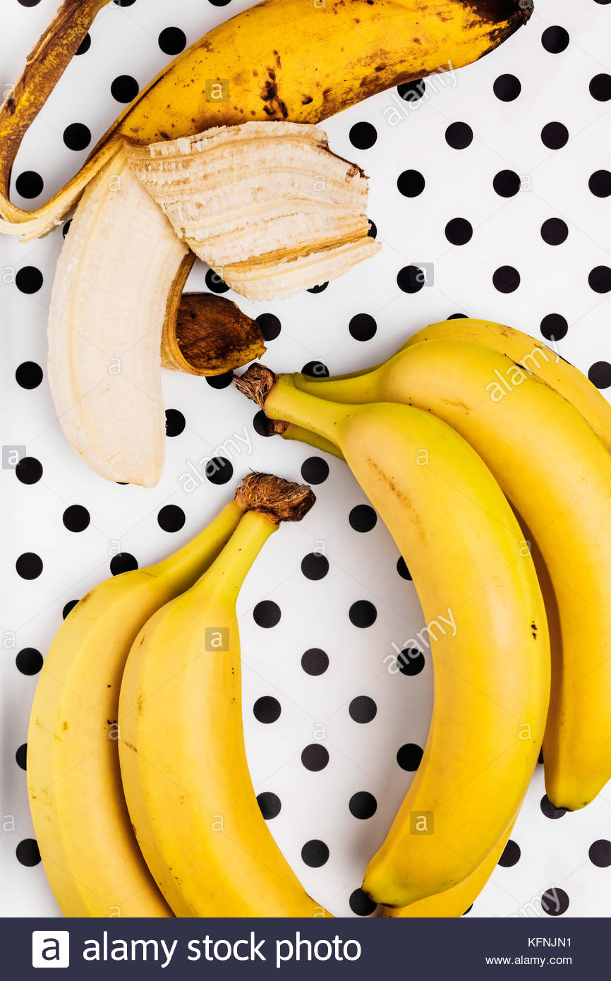 Overhead view of one overripe peeled banana together with a small bunch of ripe bananas on a polka dot background. - Stock Image