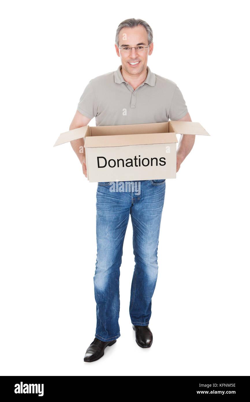 Happy man holding donation box isolated on white background - Stock Image