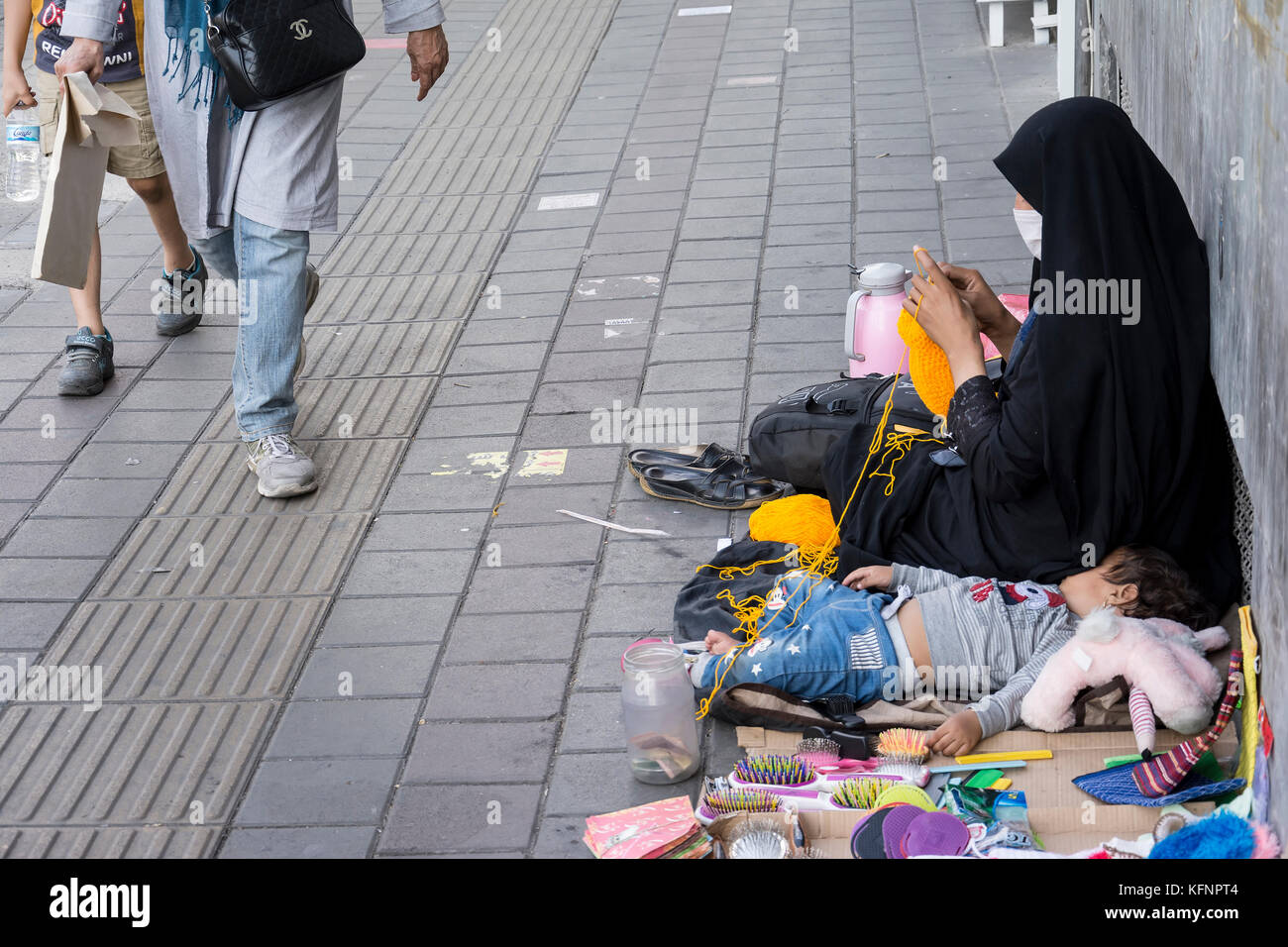 Tehran, IRAN - September 3, 2017 Street photography, muslim woman weave loofah with yellow yarn in pavement. little - Stock Image