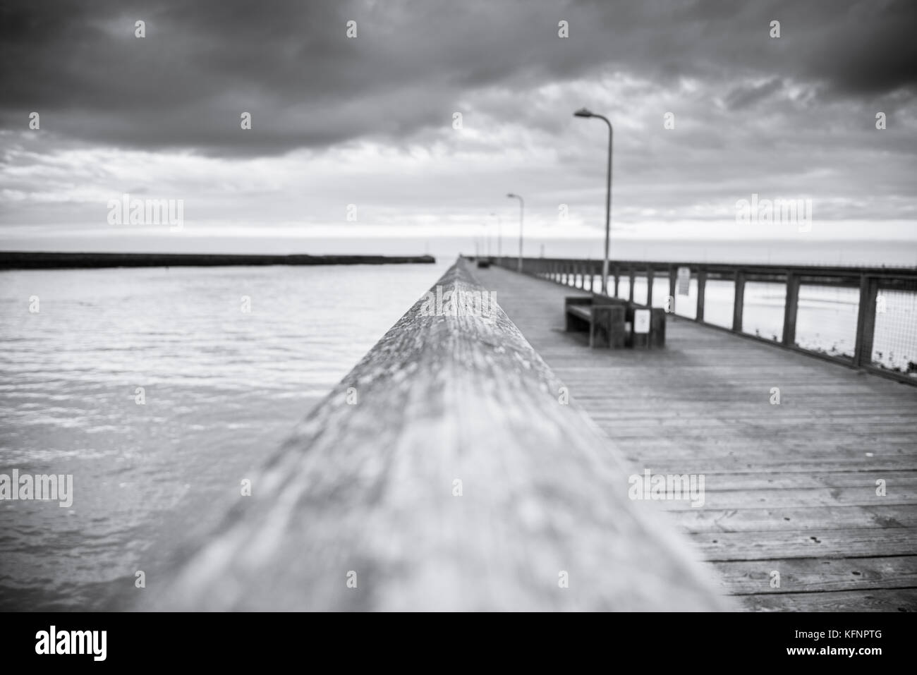 Black and white dramatic seascape - bridge, sea and clouds - Stock Image
