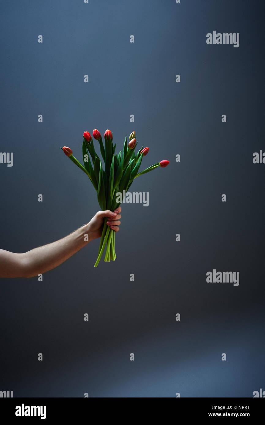 Mann streckt Blumenstrauss in die Höhe - Stock Image