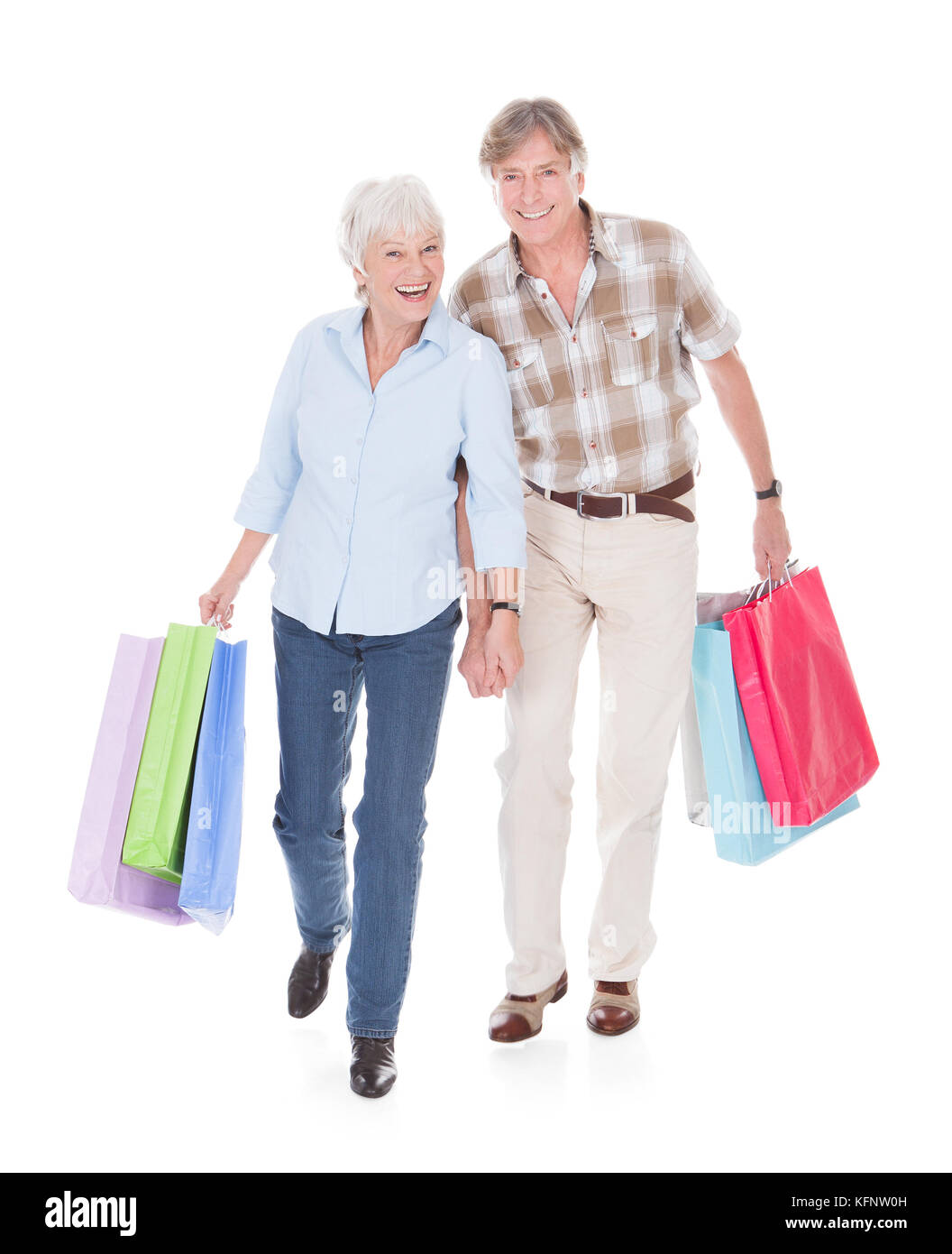 Happy Seniors Couple Walking With Shopping Bag Over White Background - Stock Image