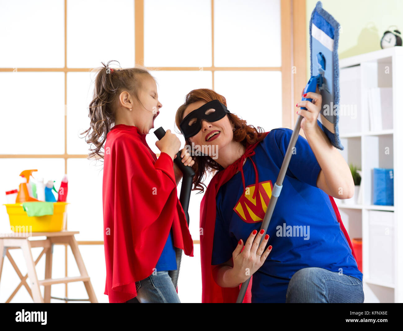 Cleaning concept. Super hero woman and daughter playing guitar and singing on cleaning equipment. Family ready to - Stock Image