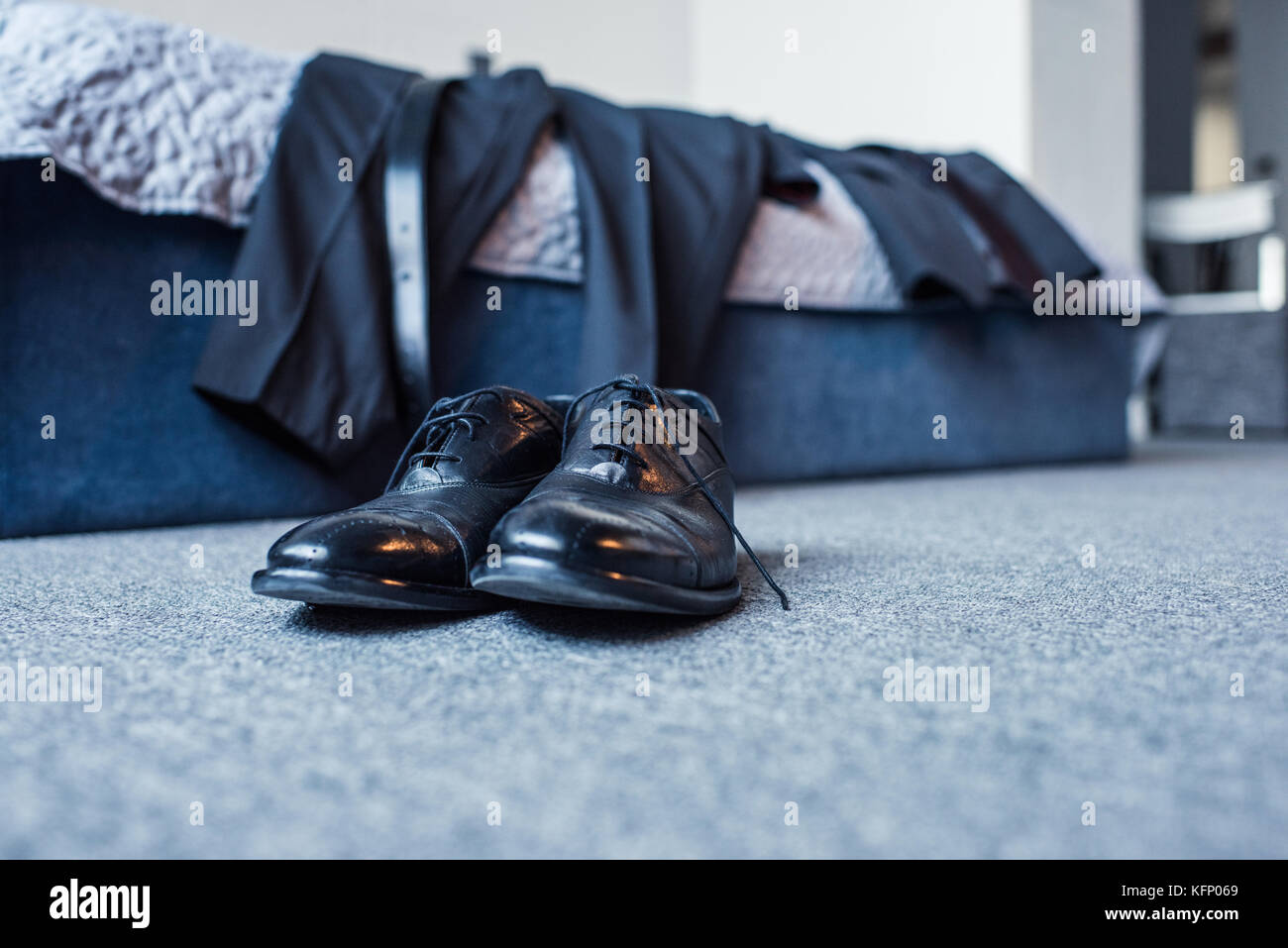 Formal attire on bed and leather shoes - Stock Image
