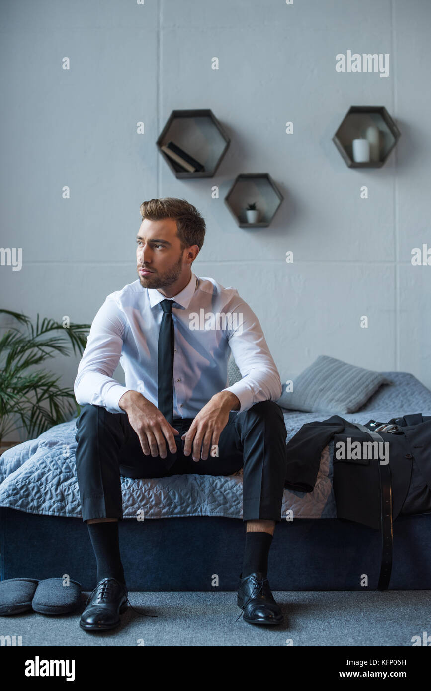 Businessman sitting on bed - Stock Image