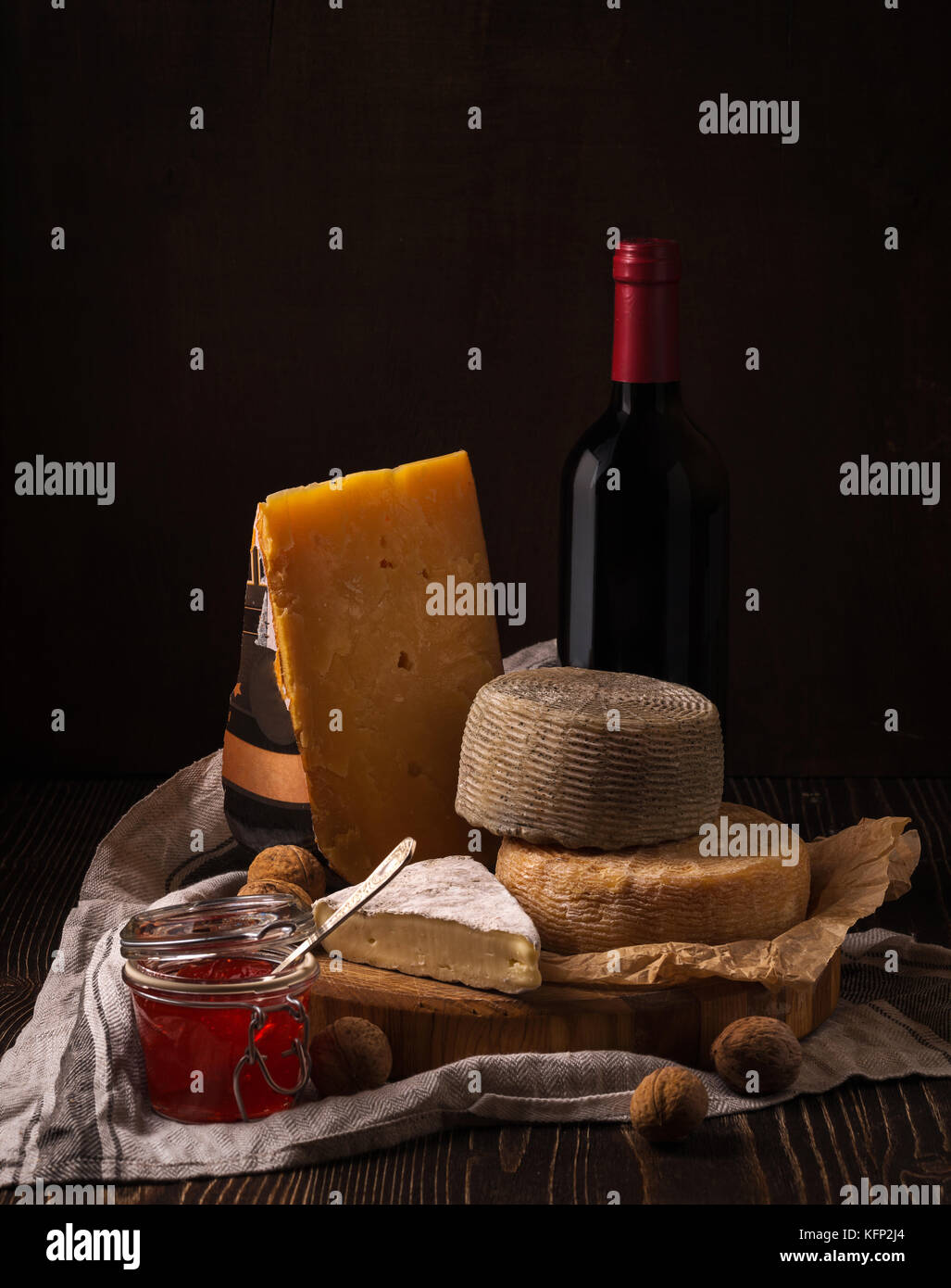 Cheese, jam and wine on the rough wood - Stock Image