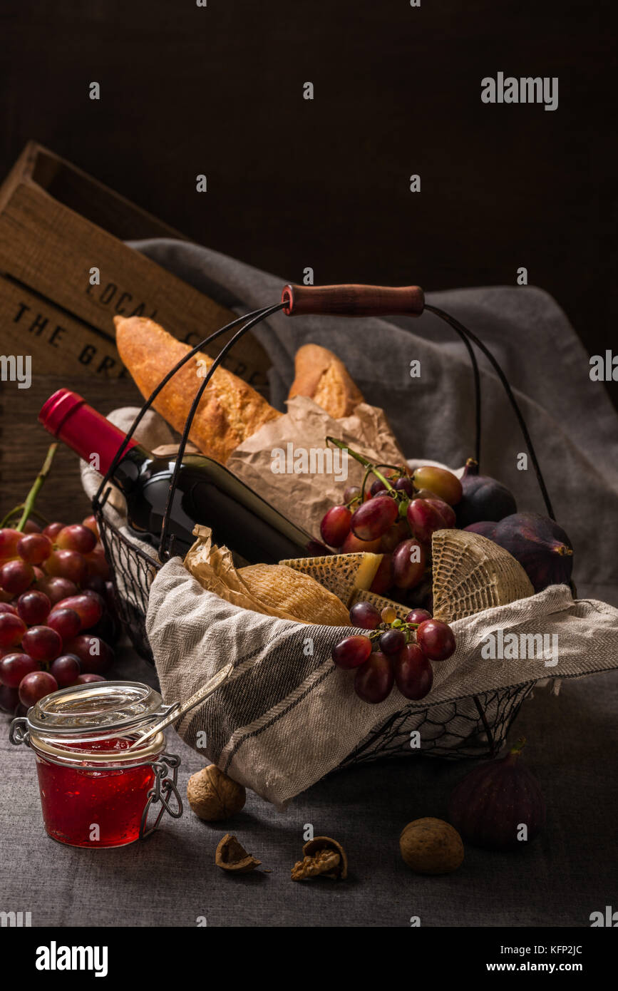 Picnic basket with cheese, fruits, bread and wine - Stock Image