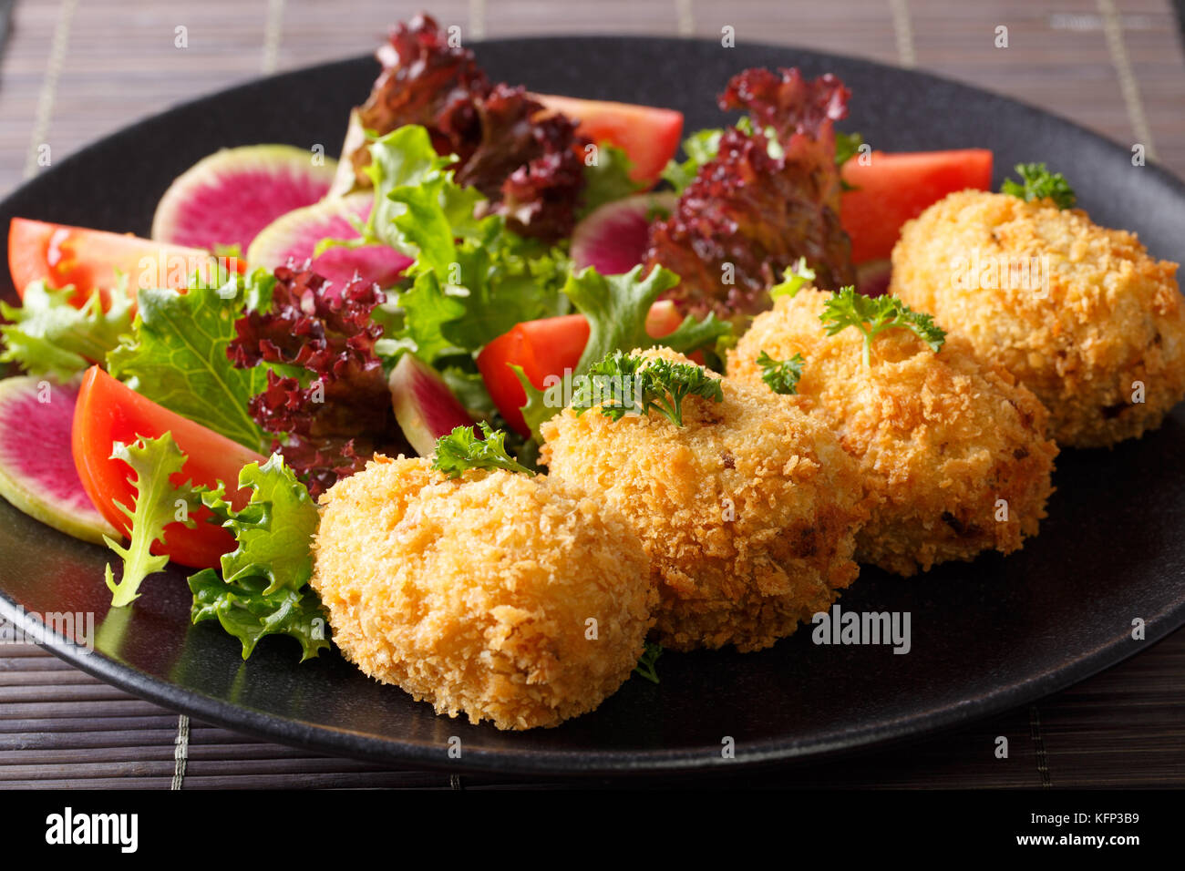 Japanese potato korokke and fresh vegetables close-up on a plate. horizontal - Stock Image