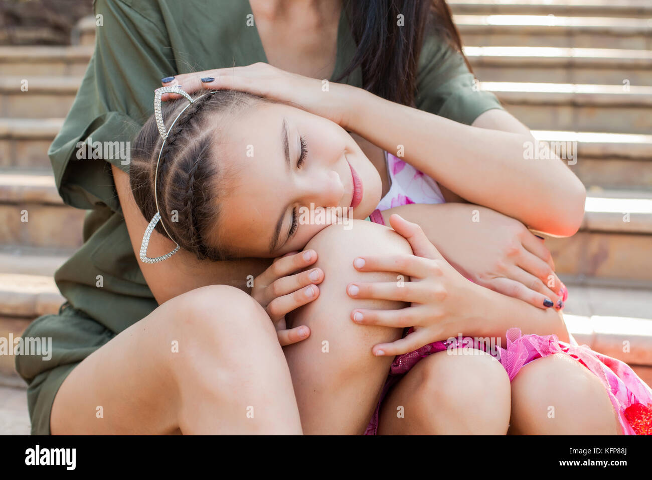 Little girl putting head on mother's knees - Stock Image