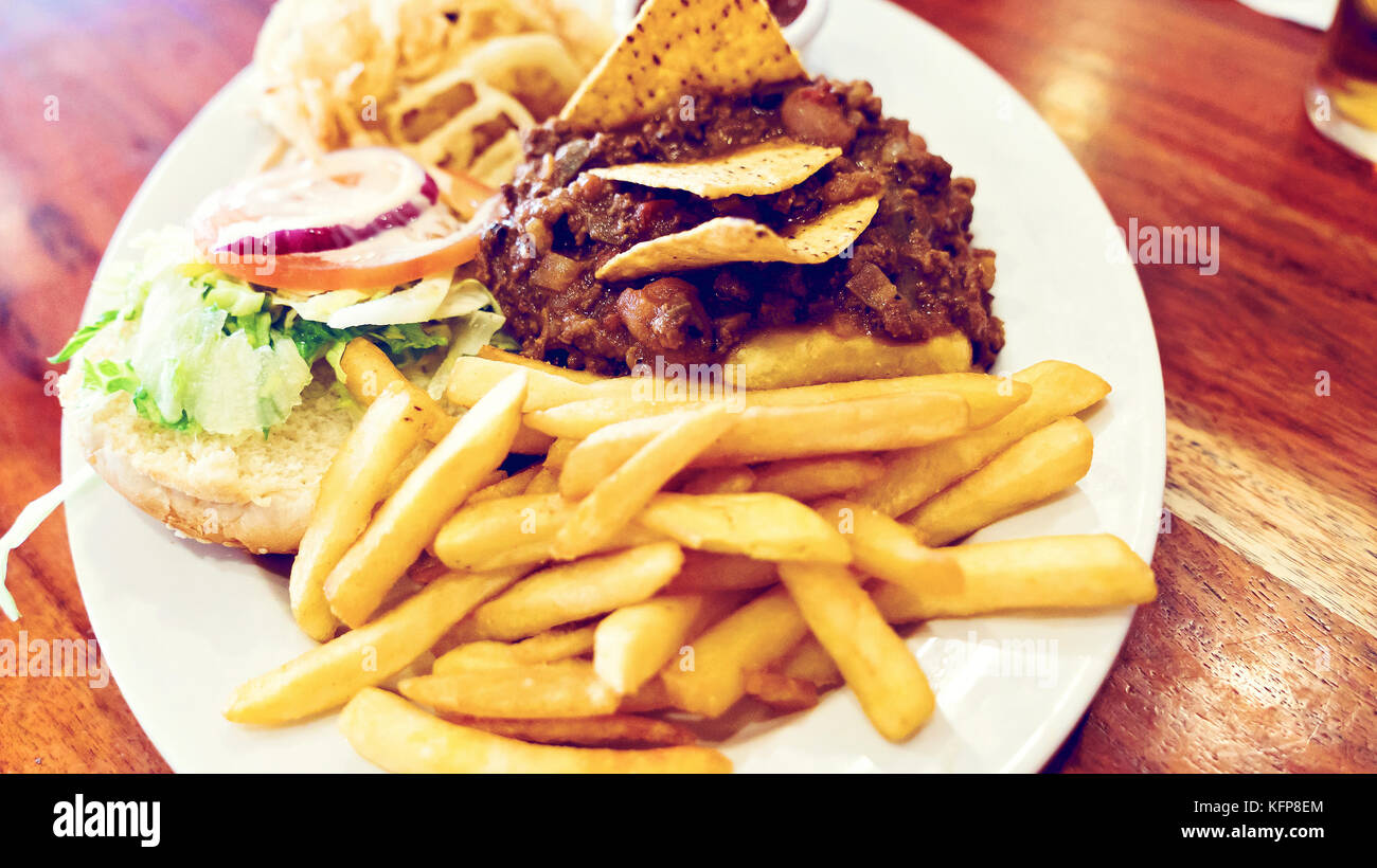 Unhealthy meal with mexican nacho chips loaded with beef, cheese, fries, onion rings and hot souse - Stock Image