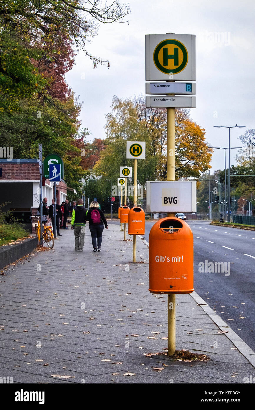Berlin Wannsee,Row of BVG Bus stop signs and orange rubbish bins  in street in Autumn - Stock Image