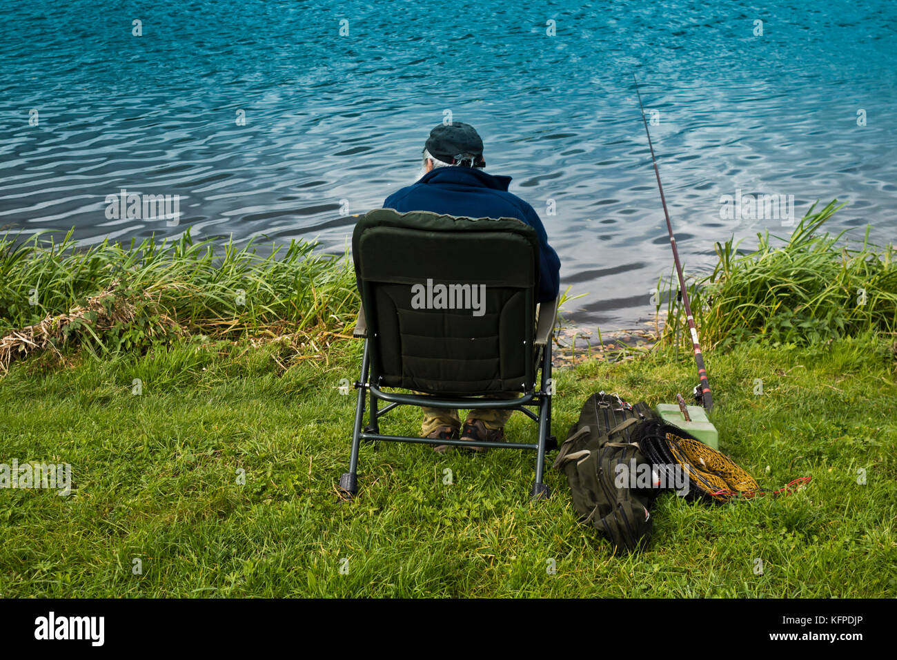 elder fisherman sitting on the riverbank and waiting to catch a fish - Stock Image