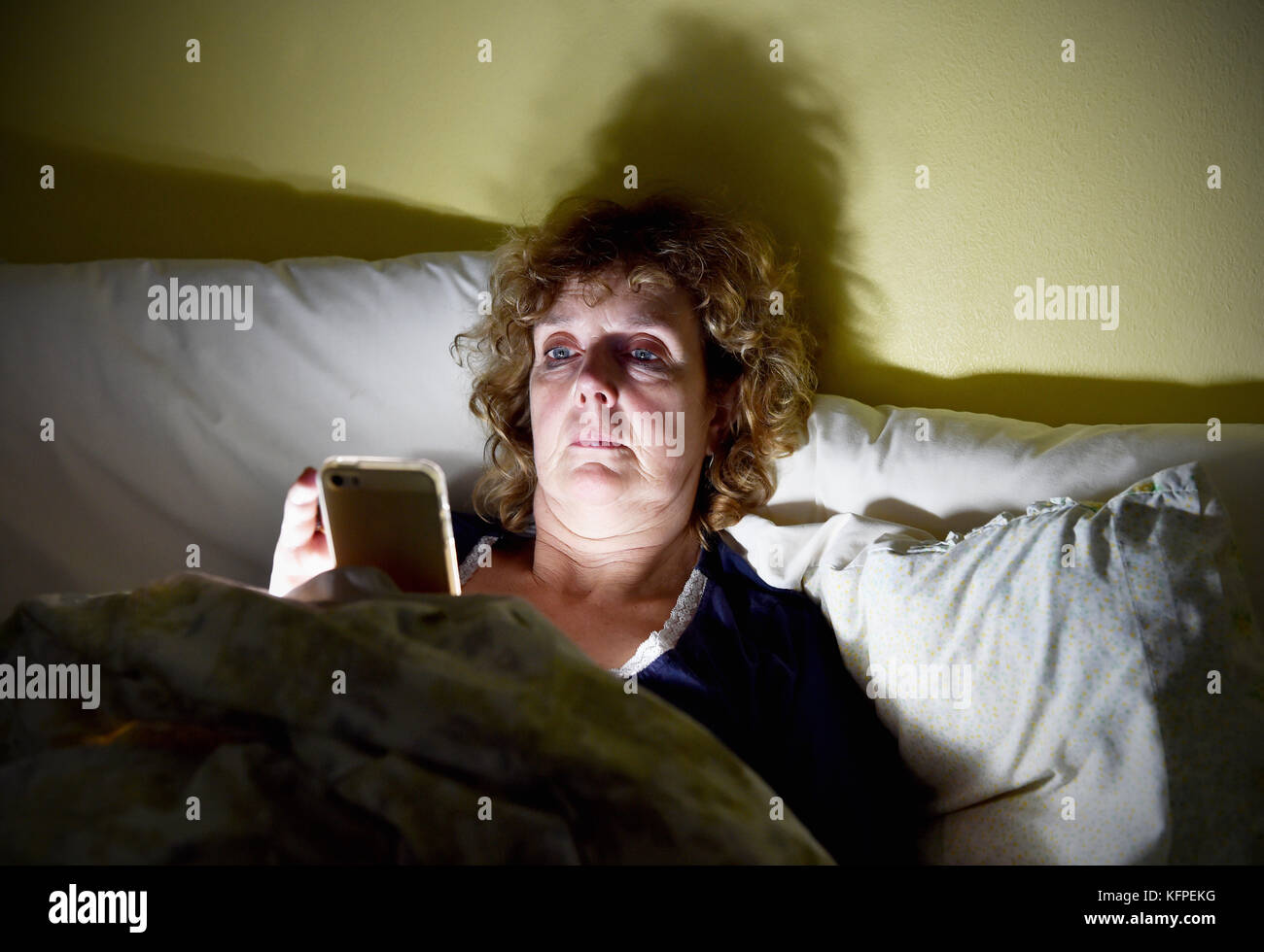 Middle aged woman reading her Apple iPhone smartphone in bed at night - Stock Image