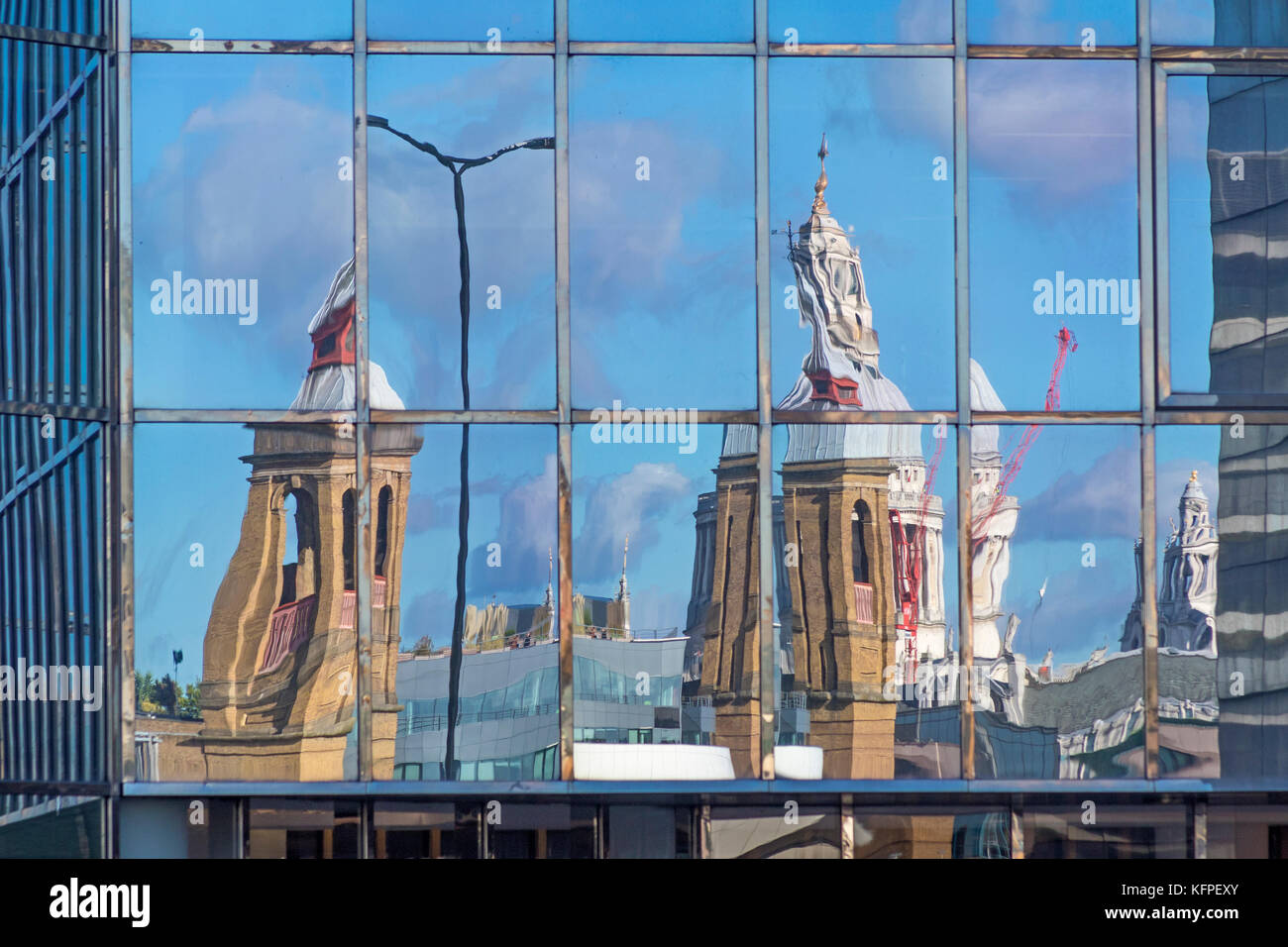 A distorted image of Cannon Street station and St Paul's Cathedral reflected in the glass frontage of an office - Stock Image
