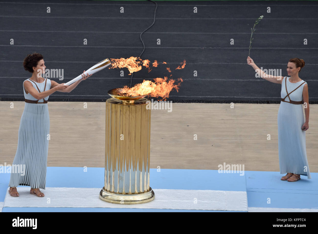 Athens, Greece, 31st October, 2017. High Priestess Katerina Lehou lights the OlympicTorch from the cauldron during - Stock Image