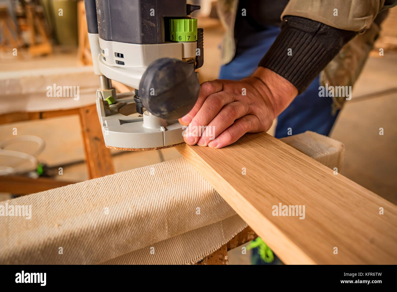 Man processing wood with router or moulding machine in a woodworking shop - Stock Image