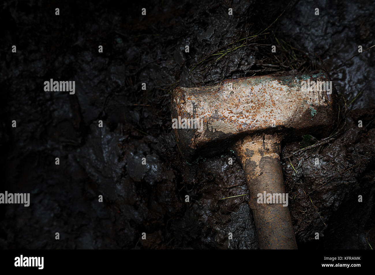 old rusty iron construction hammer on the mud, dramatic photography and low key photography. - Stock Image