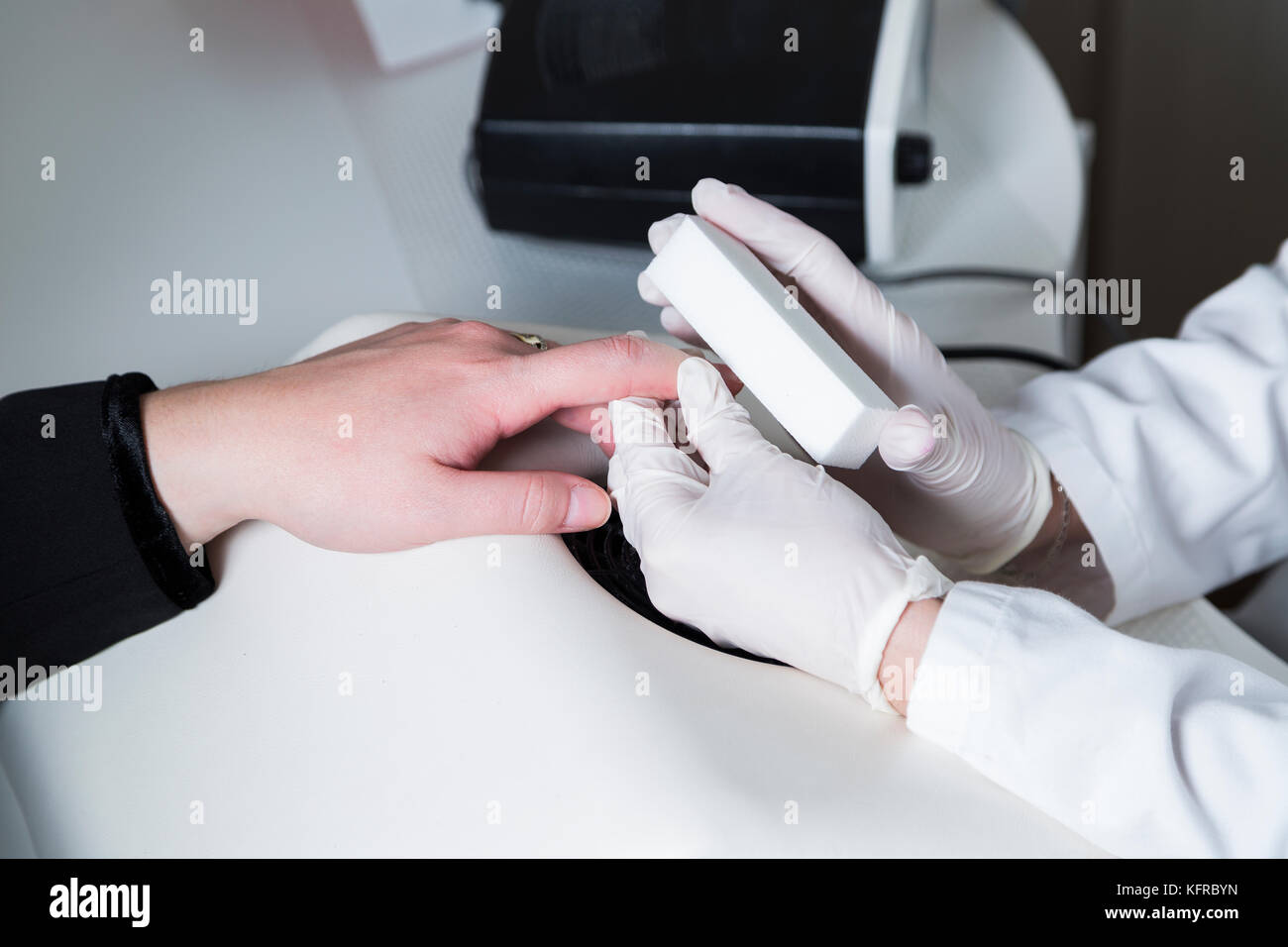 Cosmetologist beautician treats nails of patient with nailfile. - Stock Image