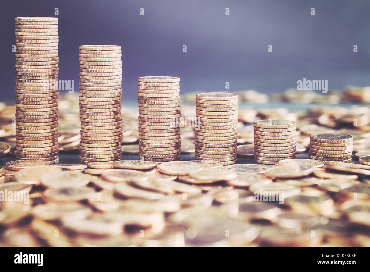 Stacks of golden coins, color toning applied. - Stock Image