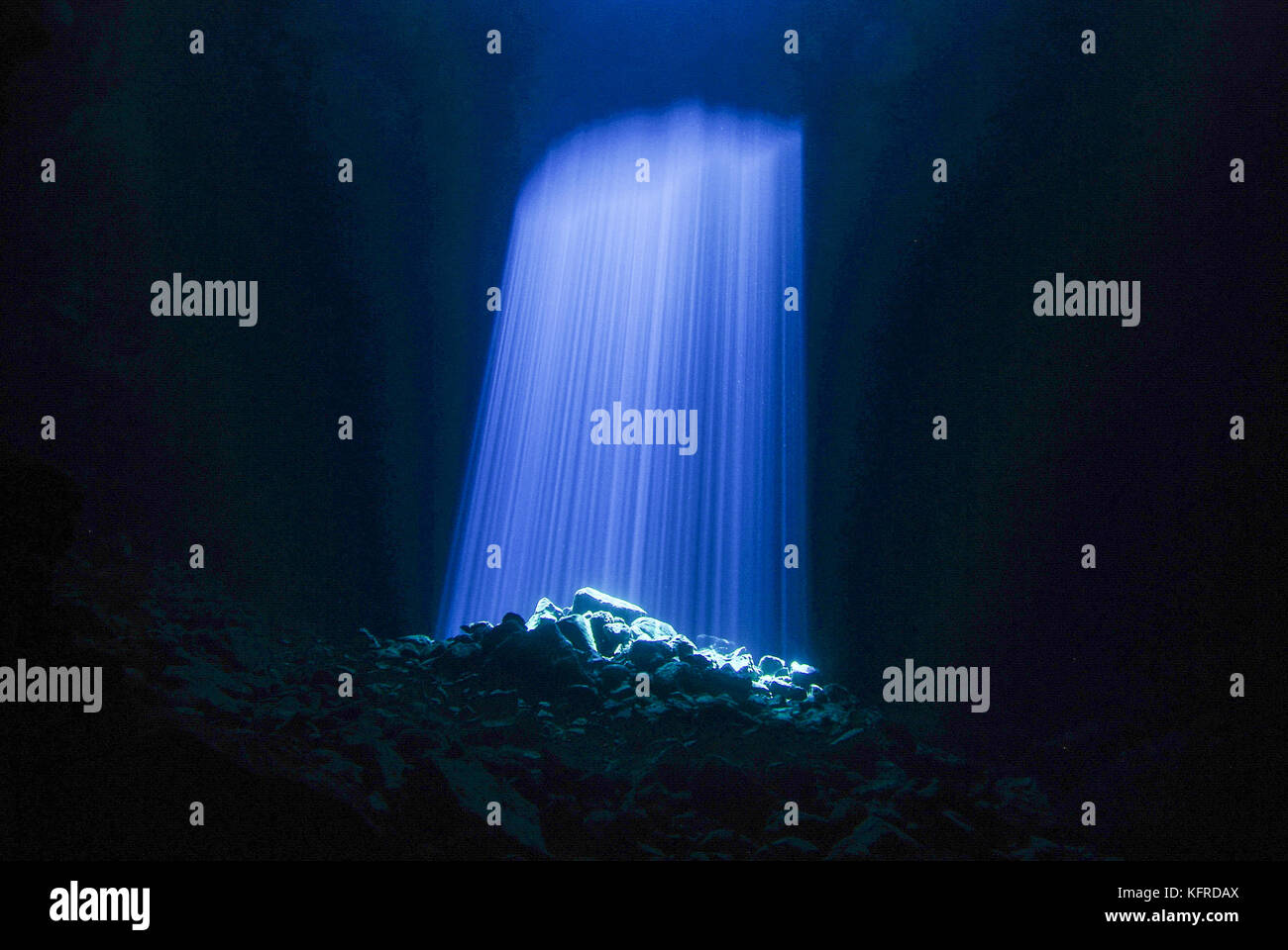 Blue Sunlight shining through hole in underwater cave Stock Photo