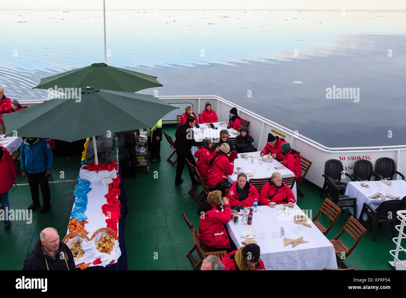 G Adventures cruise ship passengers eating outside on deck sailing through icy Arctic waters off Spitsbergen coast - Stock Image