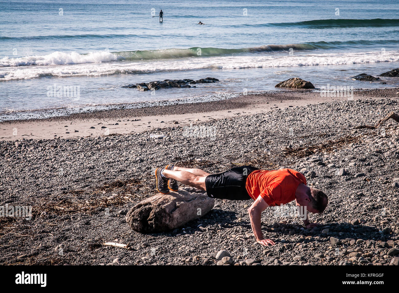 This man is working hard at his morning workout on this rocky beach,while these two surfers out on the ocean are - Stock Image